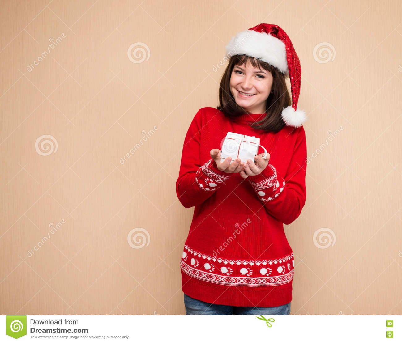 Santa Girl Holding Christmas Gift. Young Happy Woman In