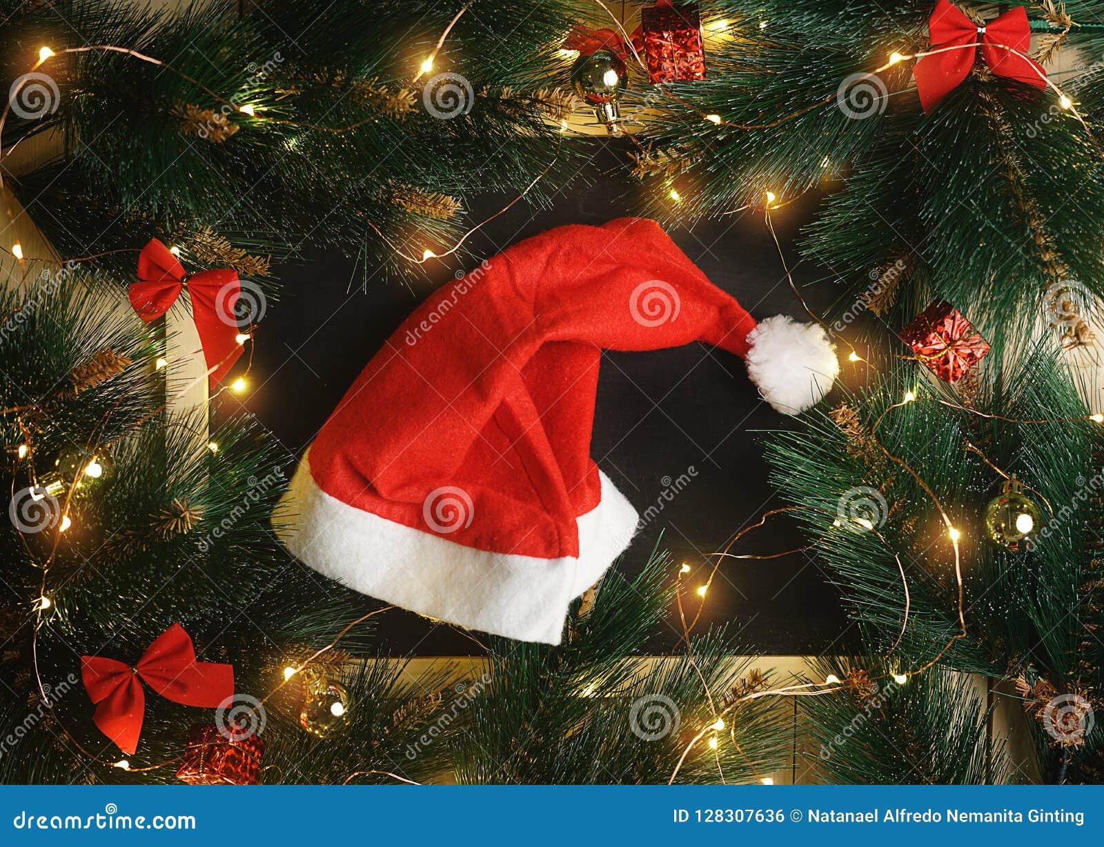 Santa Hat sur le tableau noir entouré par la lumière de Noël, ornement