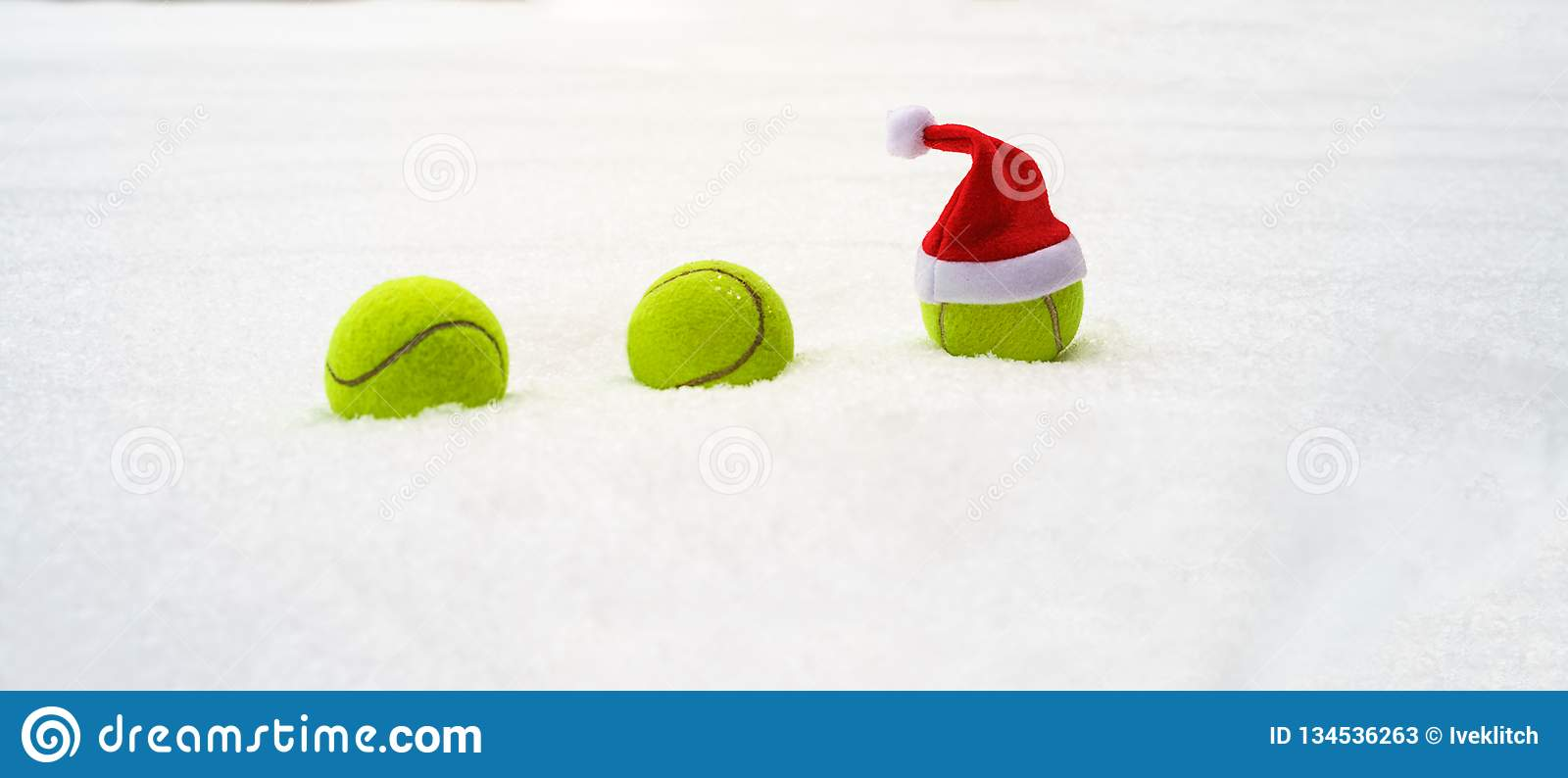 Santa hat on tennis ball on white snow background. Christmas and New year concept with tennis balls. Close up, sport lifestyle. Santa hat on tennis ball on white stock photos