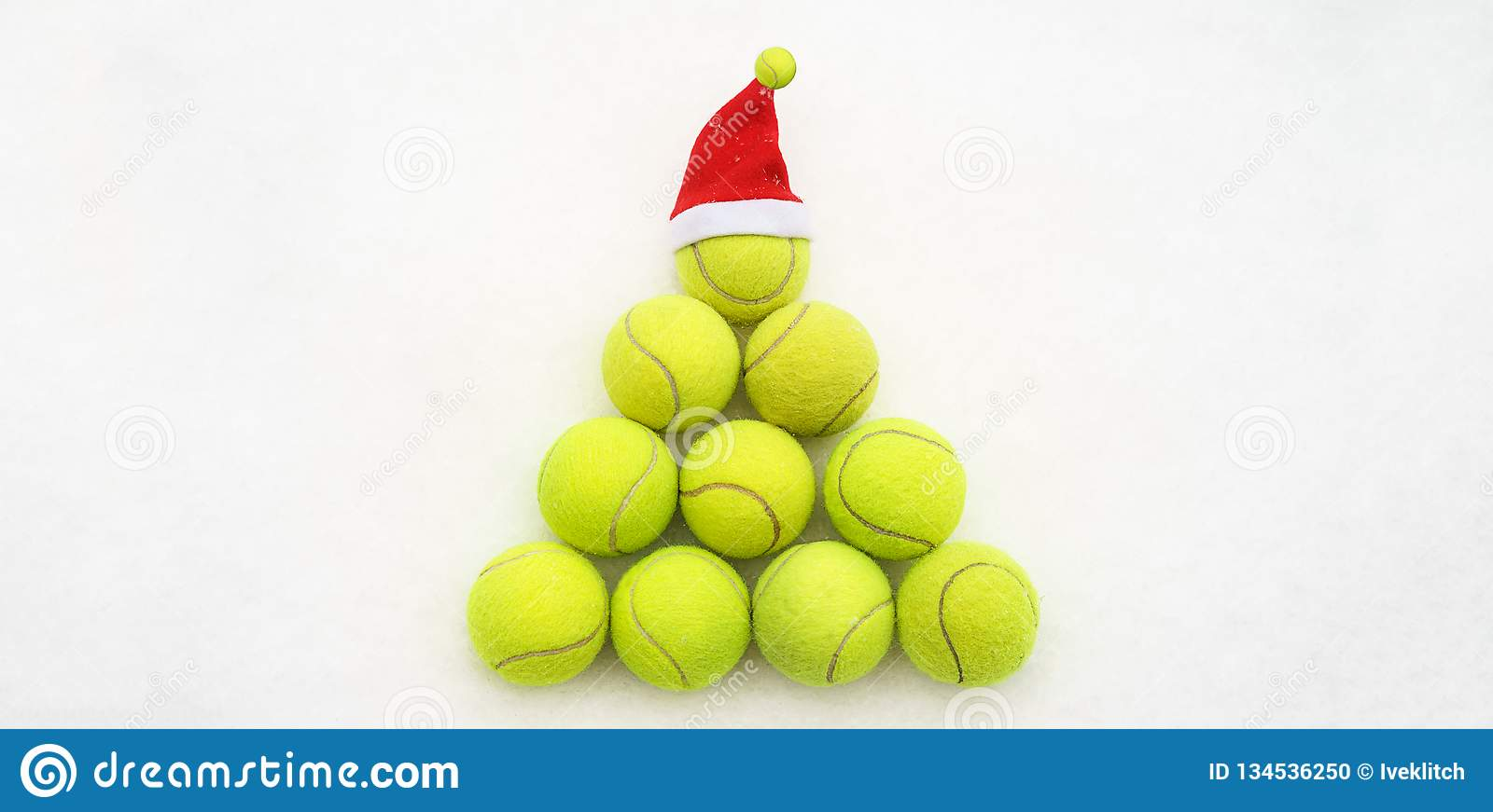 Santa hat on tennis ball on white snow background. Christmas and New year concept with tennis balls. Yellow green color tennis. Santa hat on tennis ball on white stock photo