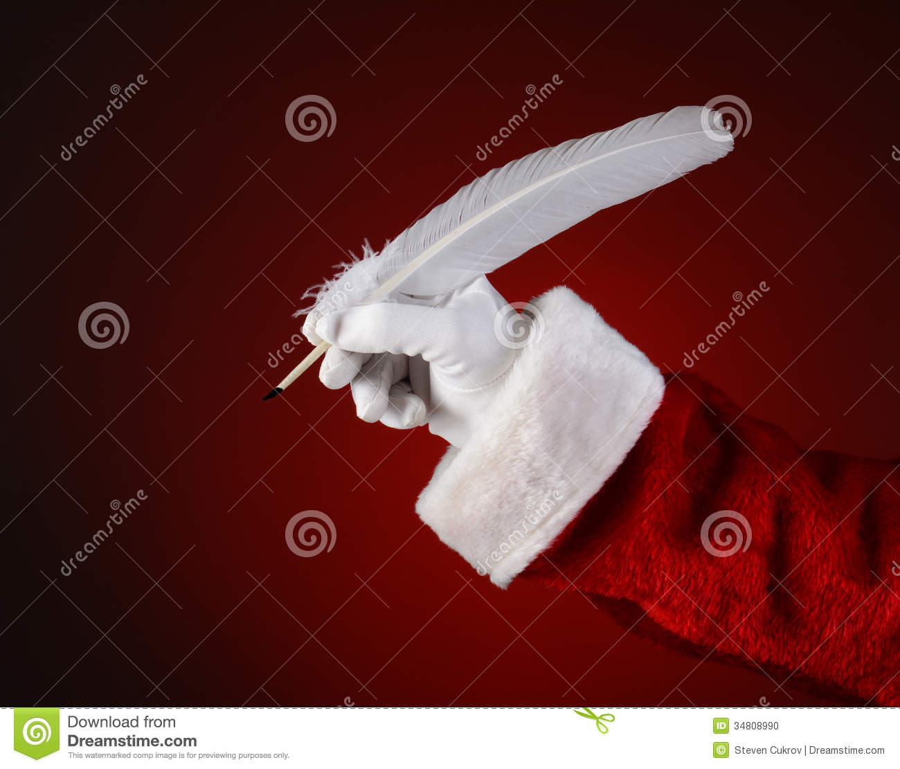santa holding a quill pen stock photo