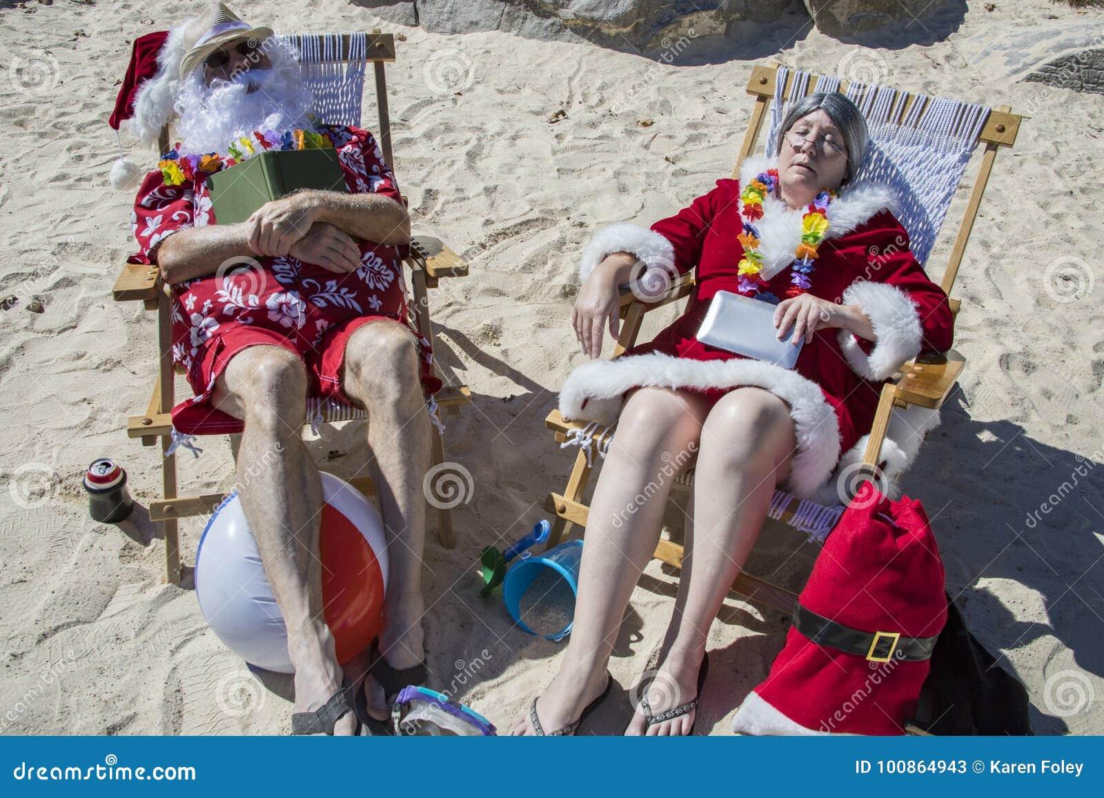 Santa i Mrs Claus dosypianie z książkami na plaży