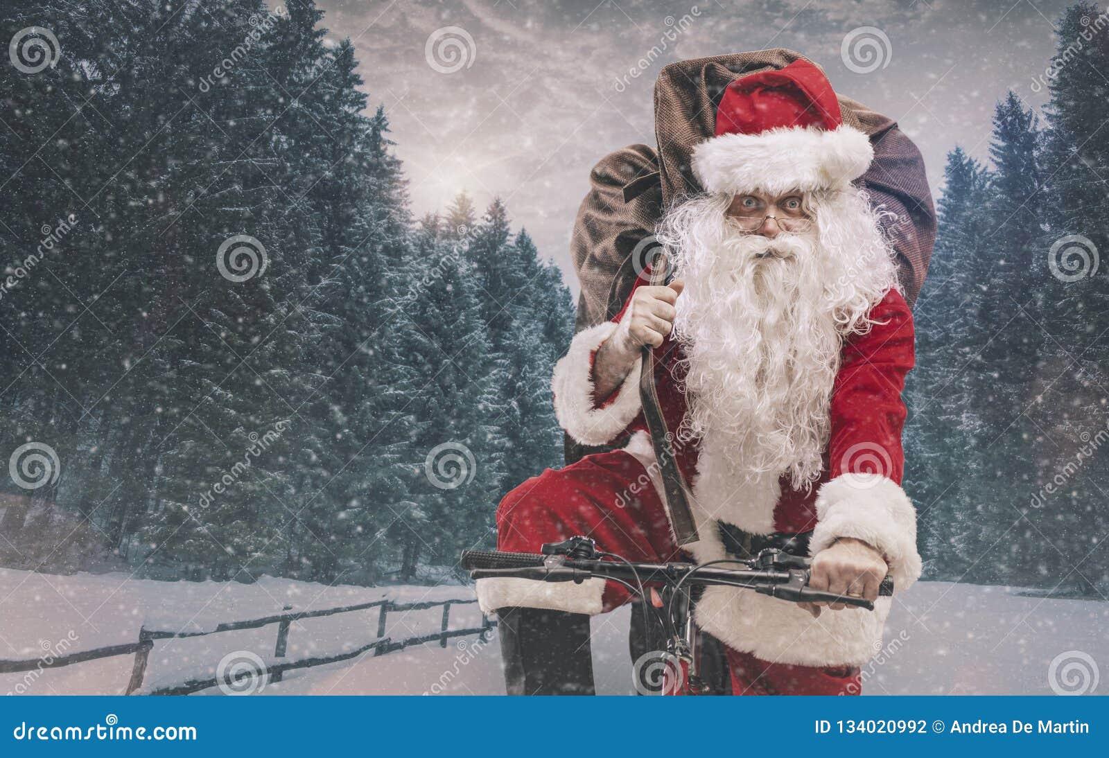 Santa montant une bicyclette et portant des cadeaux