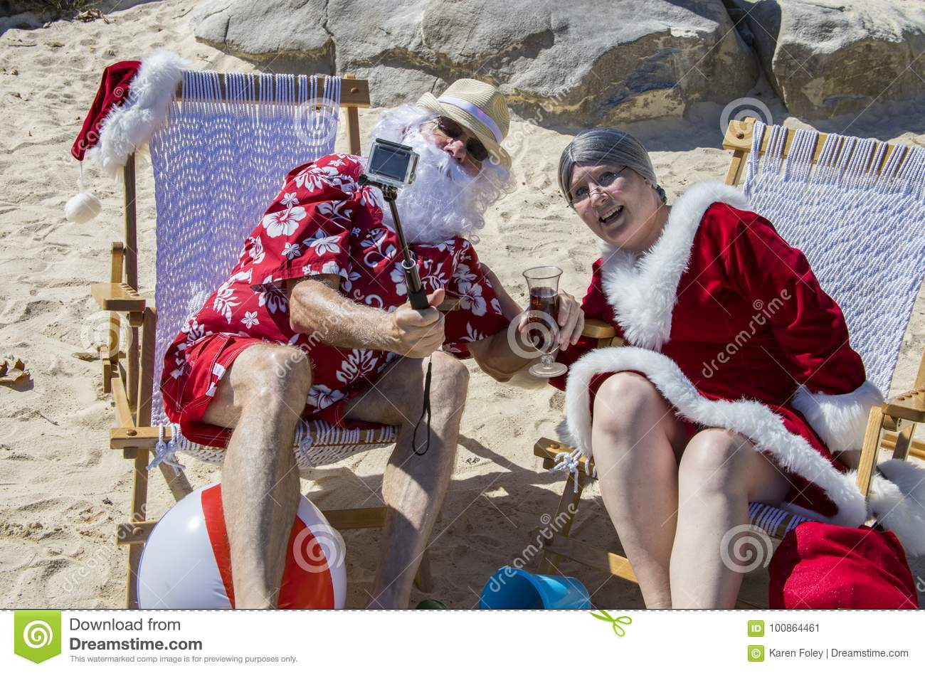 ddbd09de Santa Claus in red swimming trunks and Hawaiian shirt lounging on sandy  beach with Mrs Claus taking selfie.