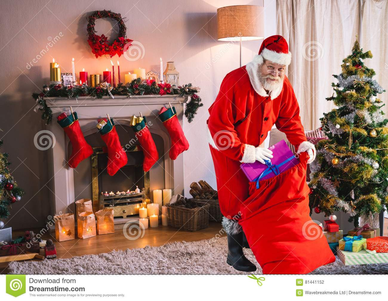 Santa Putting Christmas Gifts In Sack In Living Room Stock Photo ...