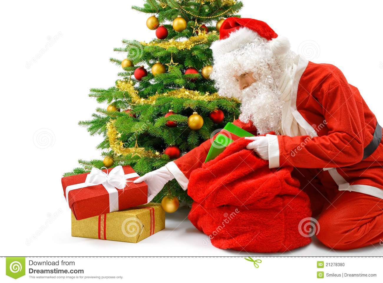 Santa Putting Gifts Under The Christmas Tree Stock Photo
