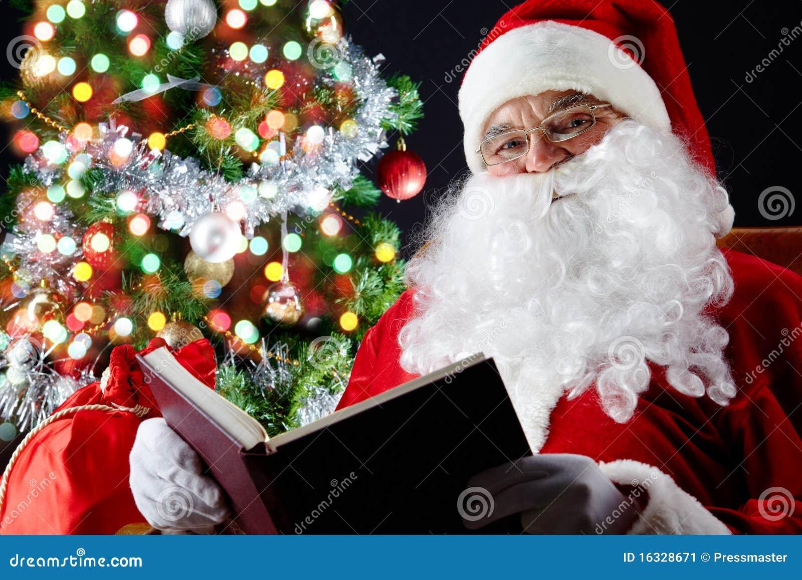 santa reading a book stock image