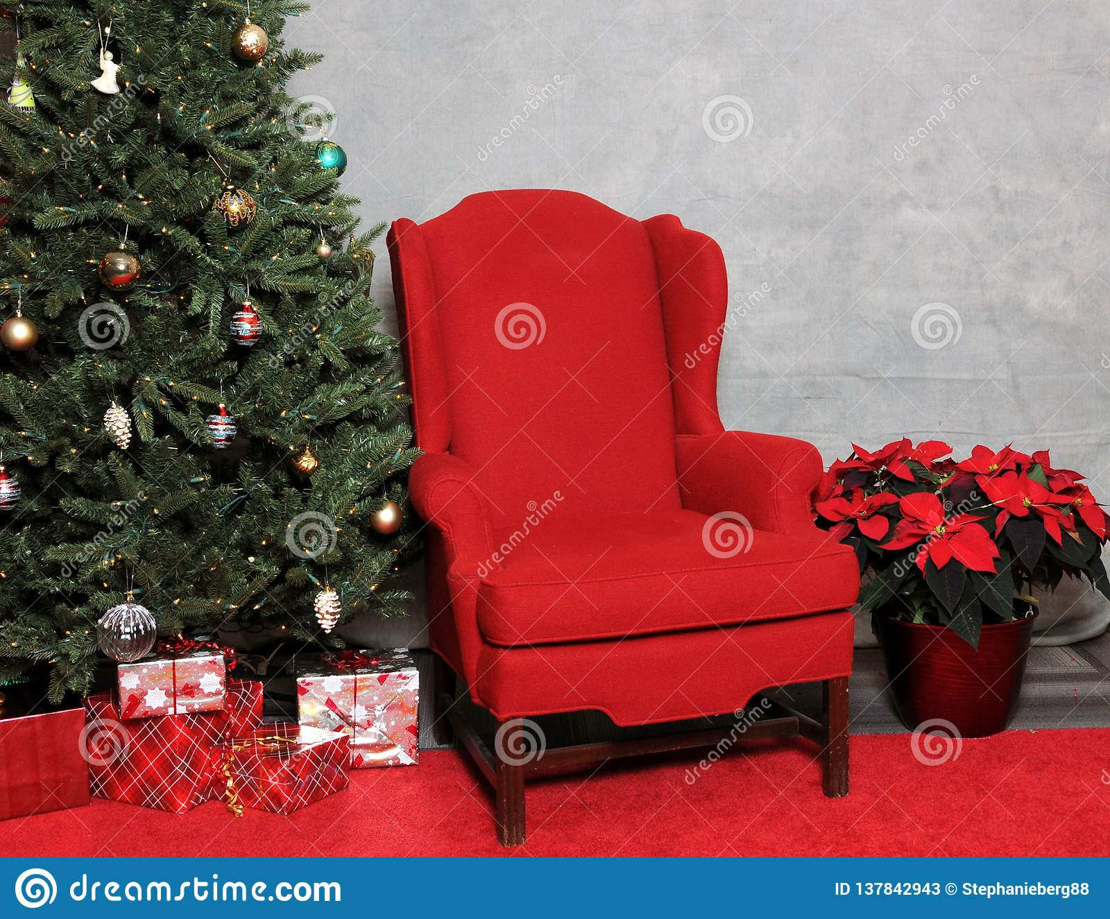 Santa`s Red Chair with Gifts and a Decorated Christmas Tree