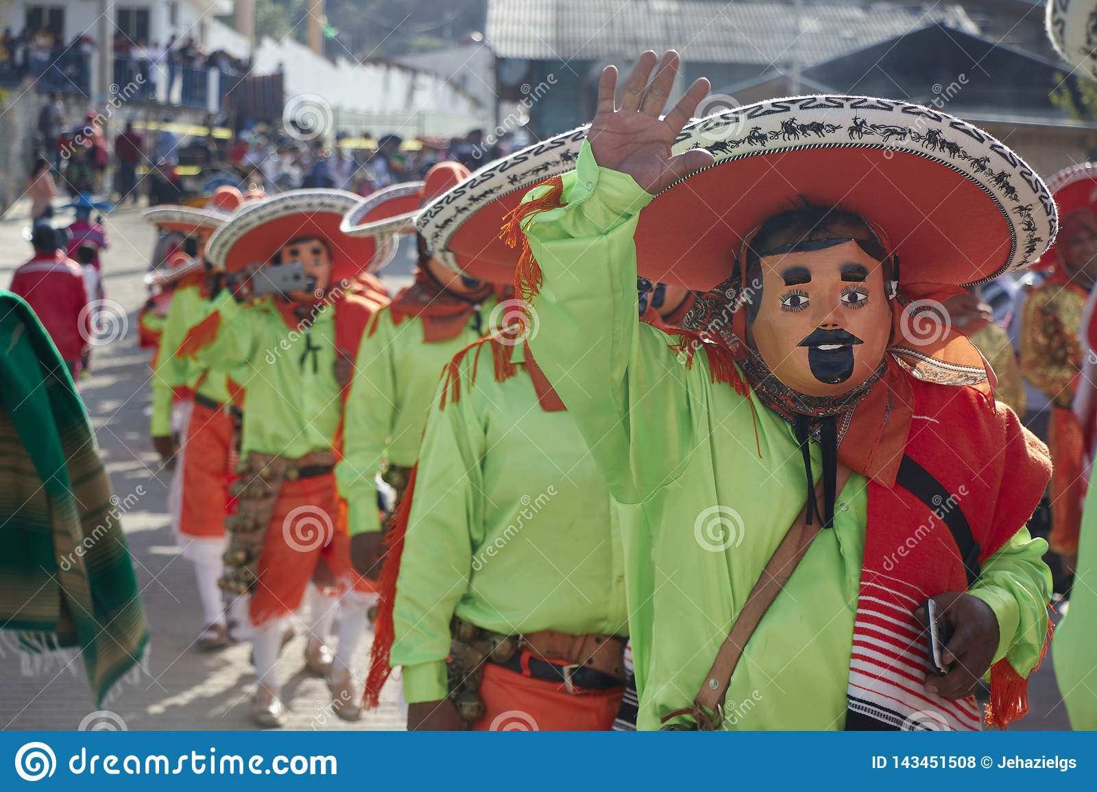 People greeting, using masks, disguised as mariachi with green shirts and orange hats
