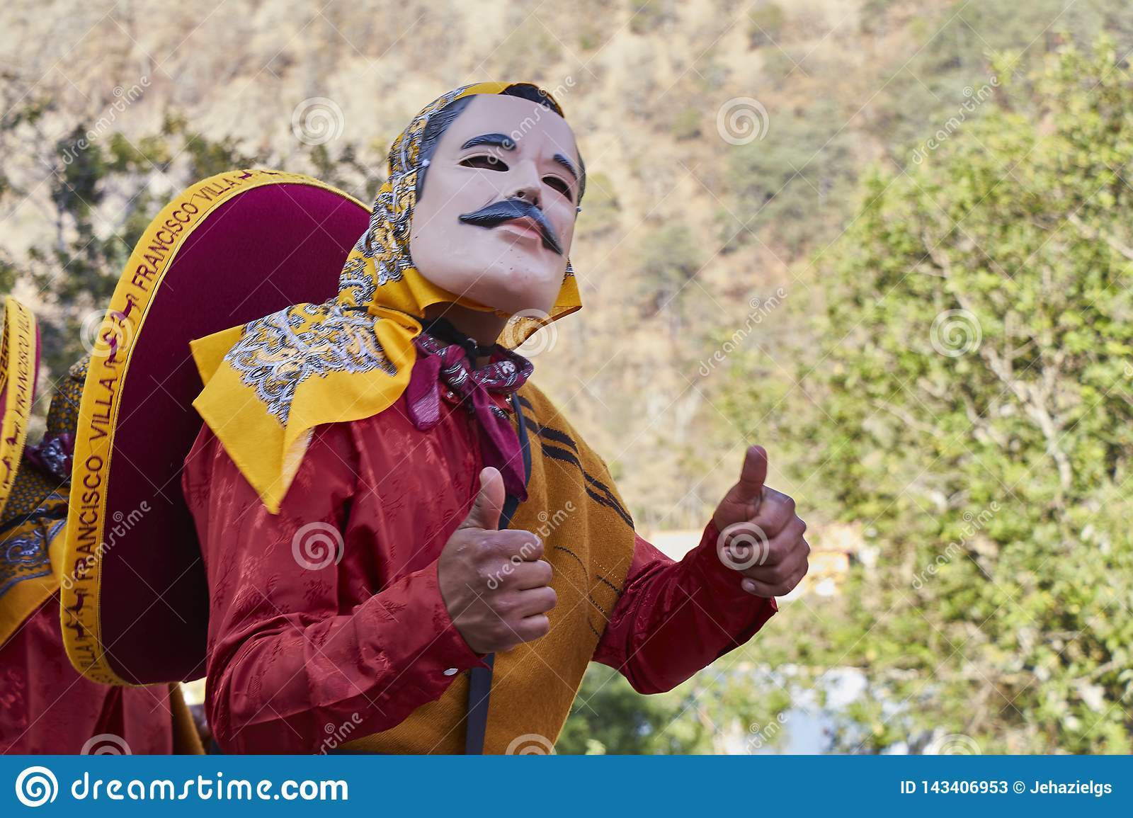 Person doing thumbs up, with mask with mustache, red dress and mexican
