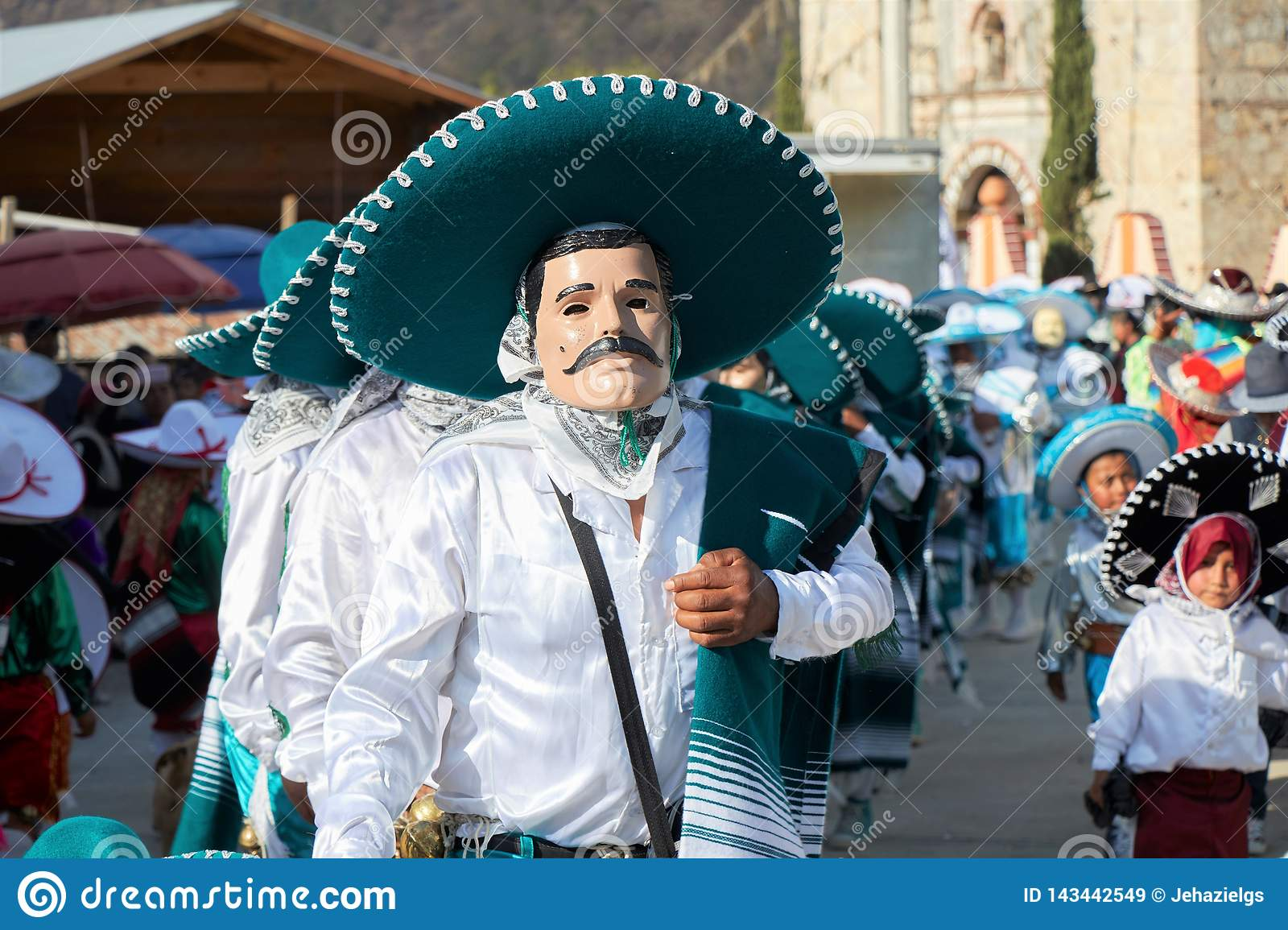 Person wearing mask and disguised as mariachi with dark green hat during a