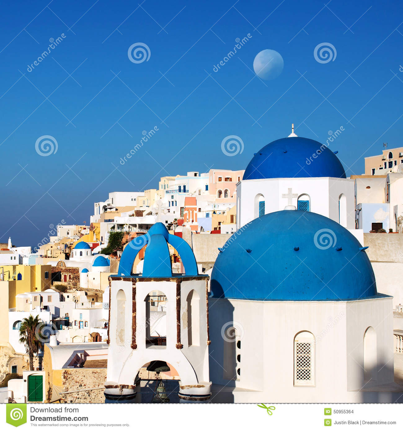 Santorini blue dome churches with moon. Oia Village, Greece.