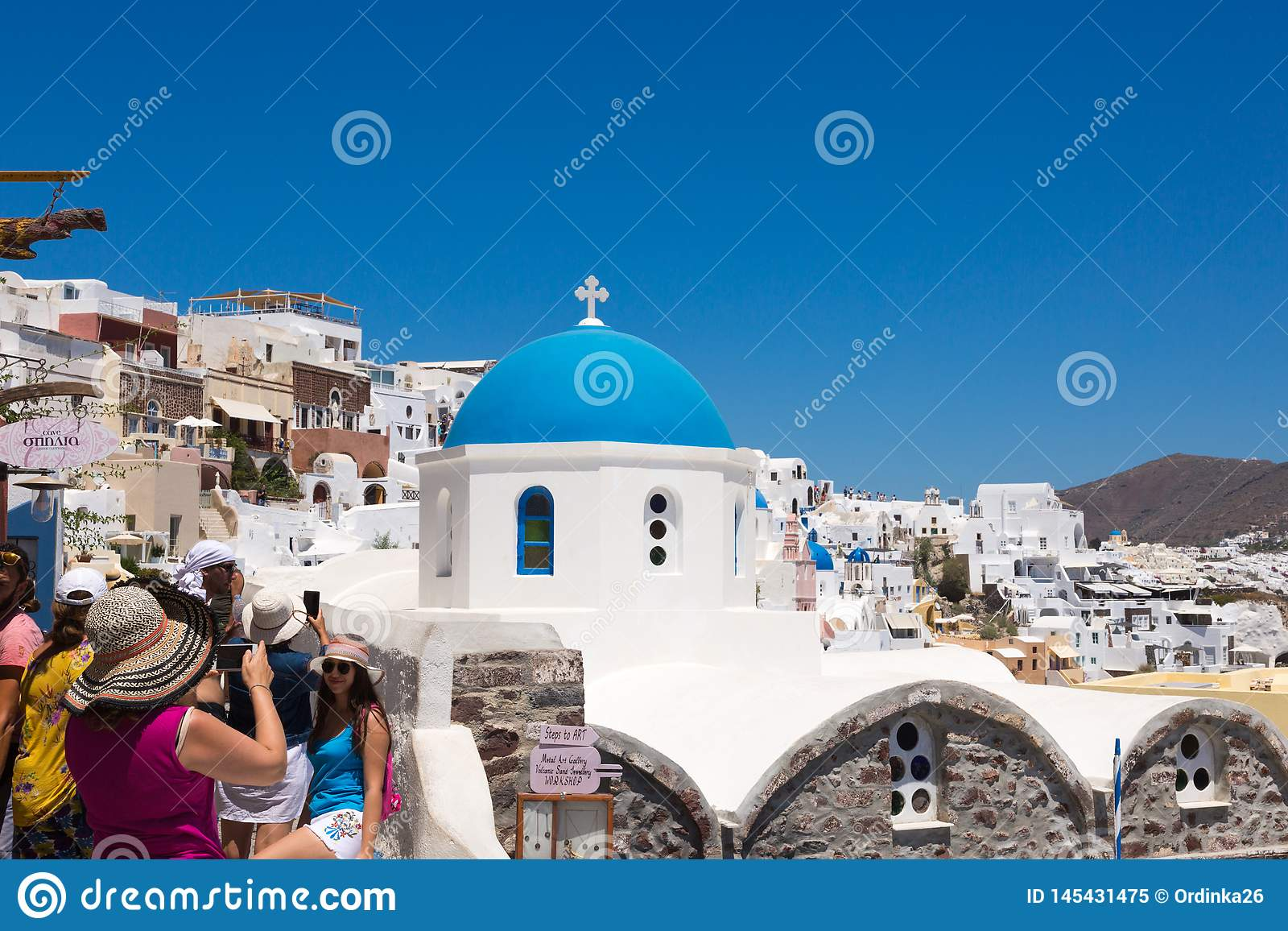 Santorini, Grecia: I turisti della gente fanno le foto sulla cupola blu del fondo della chiesa