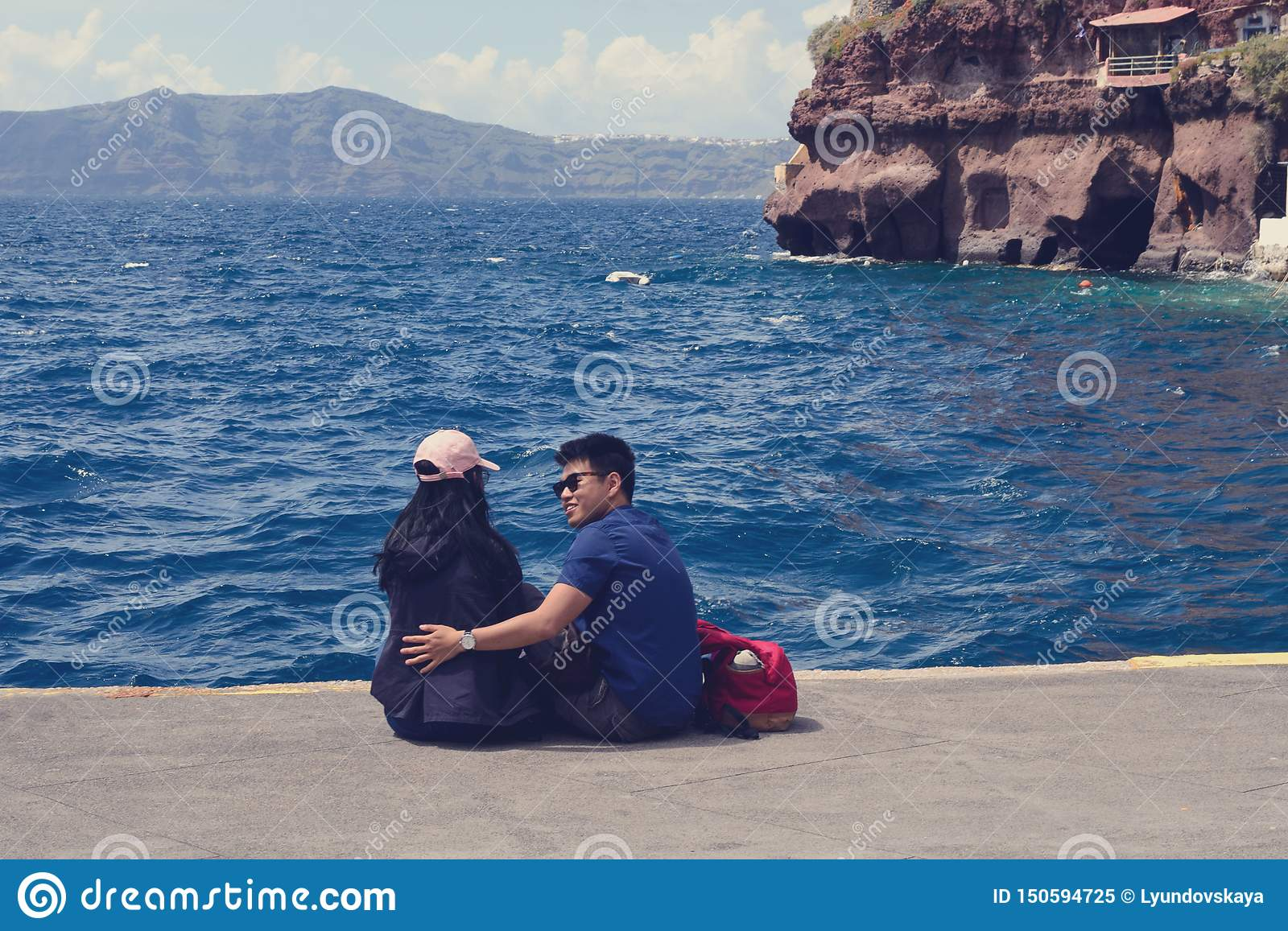 A young Chinese couple in love is sitting in the old port of the Greek city of Fira on the island of Santorini.