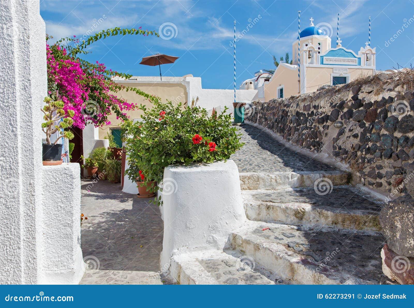 Santorini - spojrzenie piękny z decored kwiat domowym i małym typowo błękitnym kościół w Oia