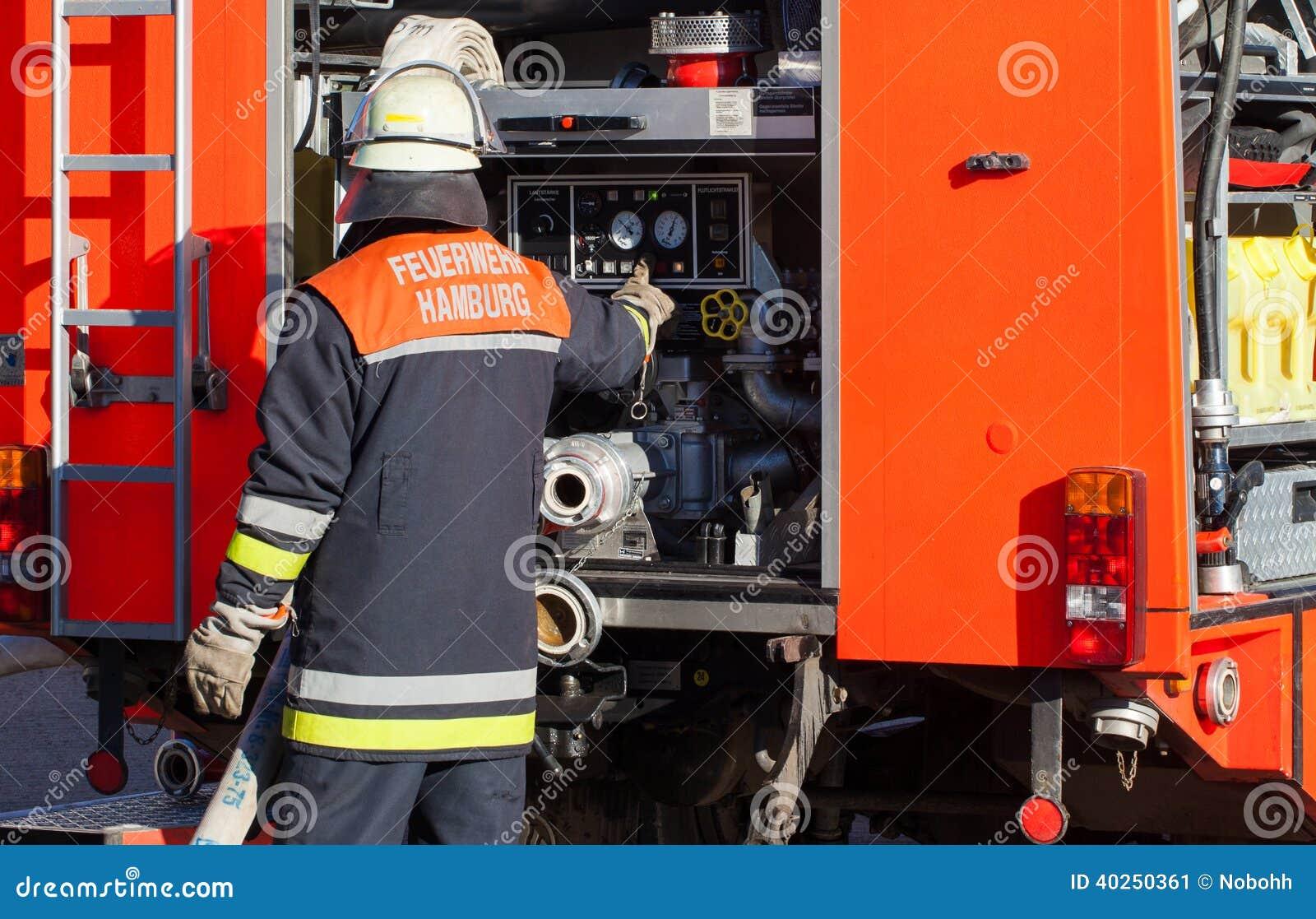 Sapador-bombeiro alemão do departamento dos bombeiros no carro de bombeiros