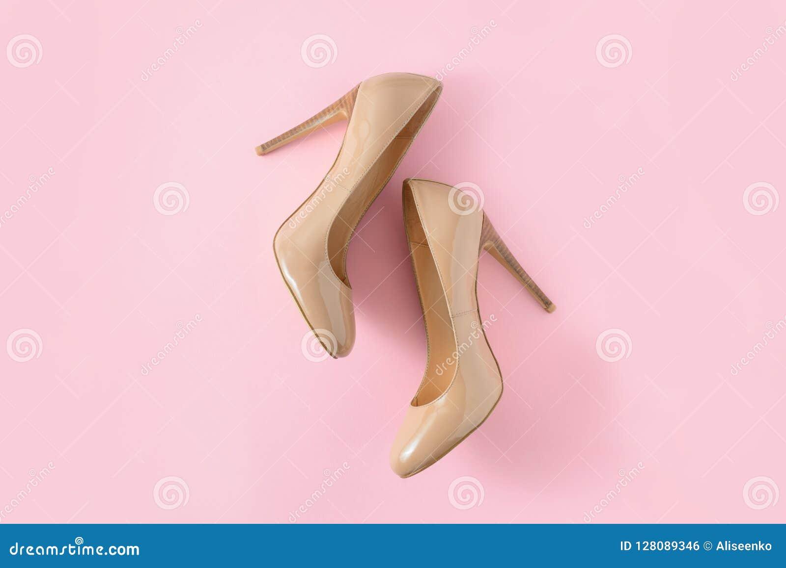 Sapatas bege do salto alto das mulheres no fundo cor-de-rosa Olhar do blogue da forma Vista superior, configuração lisa