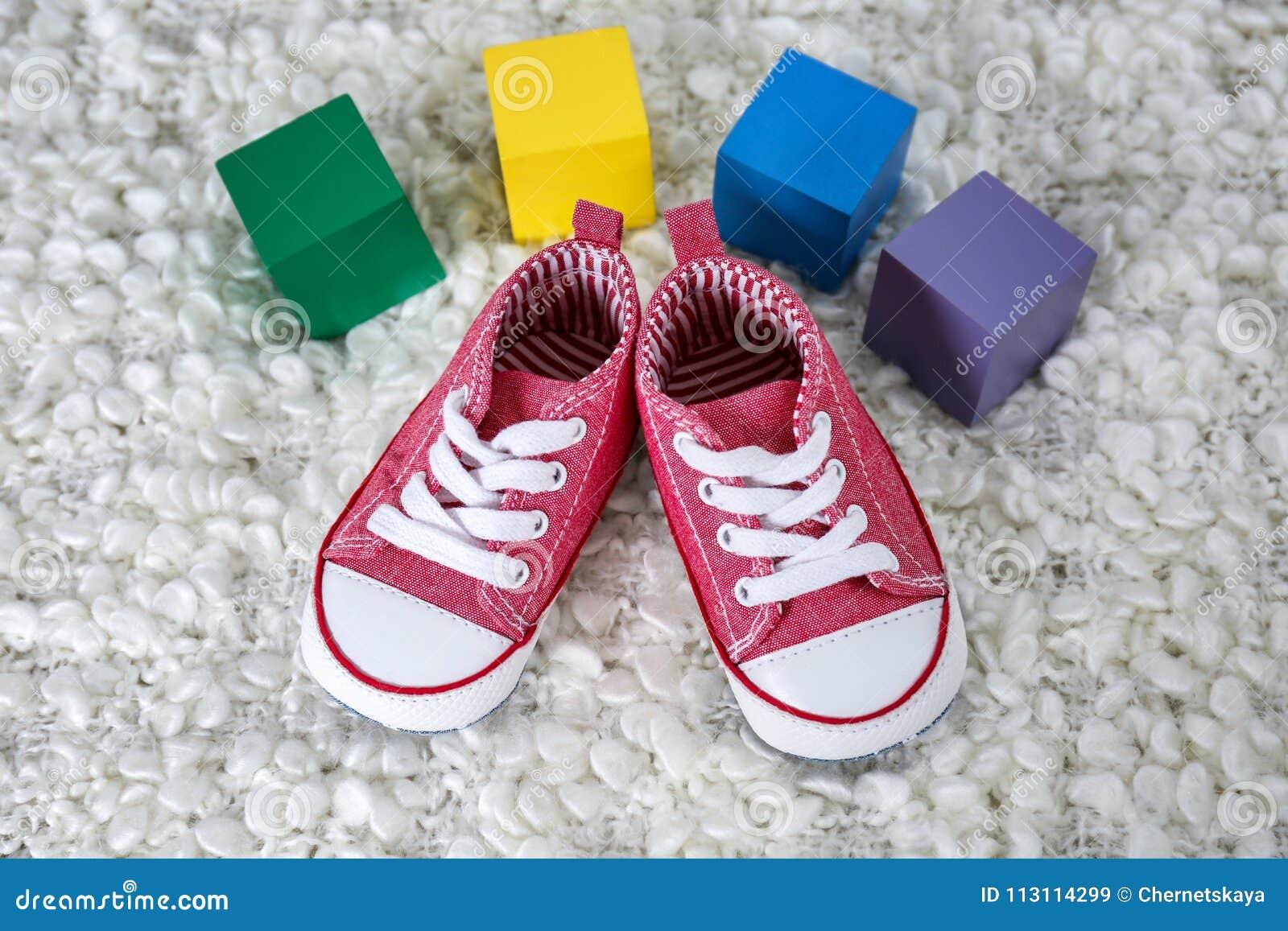 Sapatas de bebê bonitos e cubos coloridos com lugar
