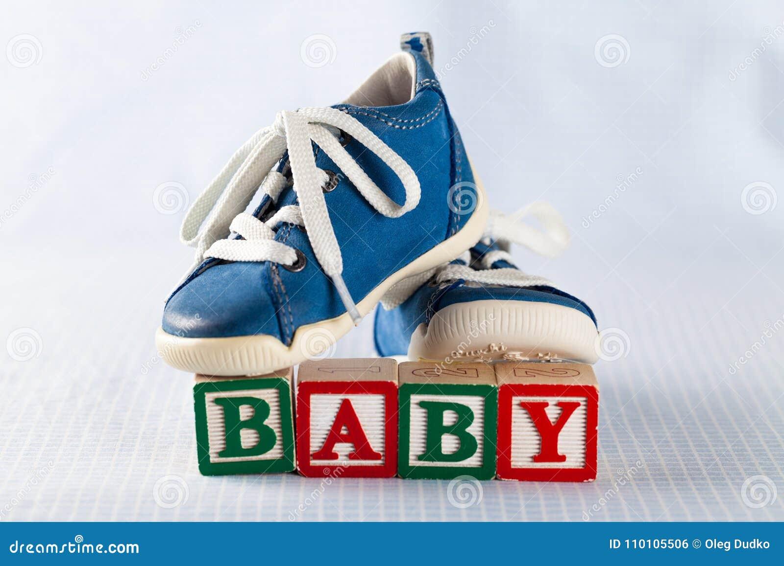 Sapatas de bebê e tijolos do brinquedo com bebê da palavra