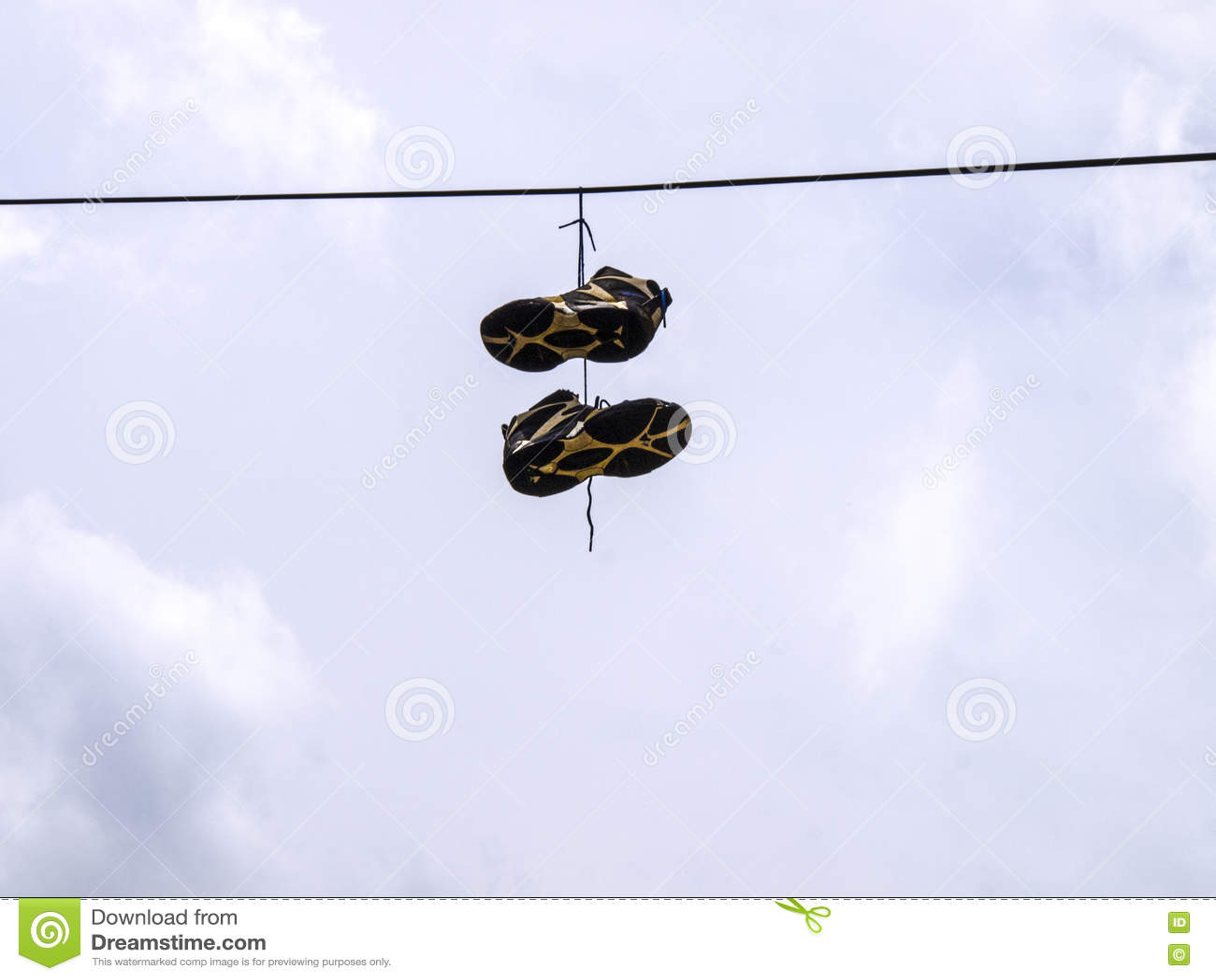 Sapatas de tênis que penduram de uma linha eléctrica