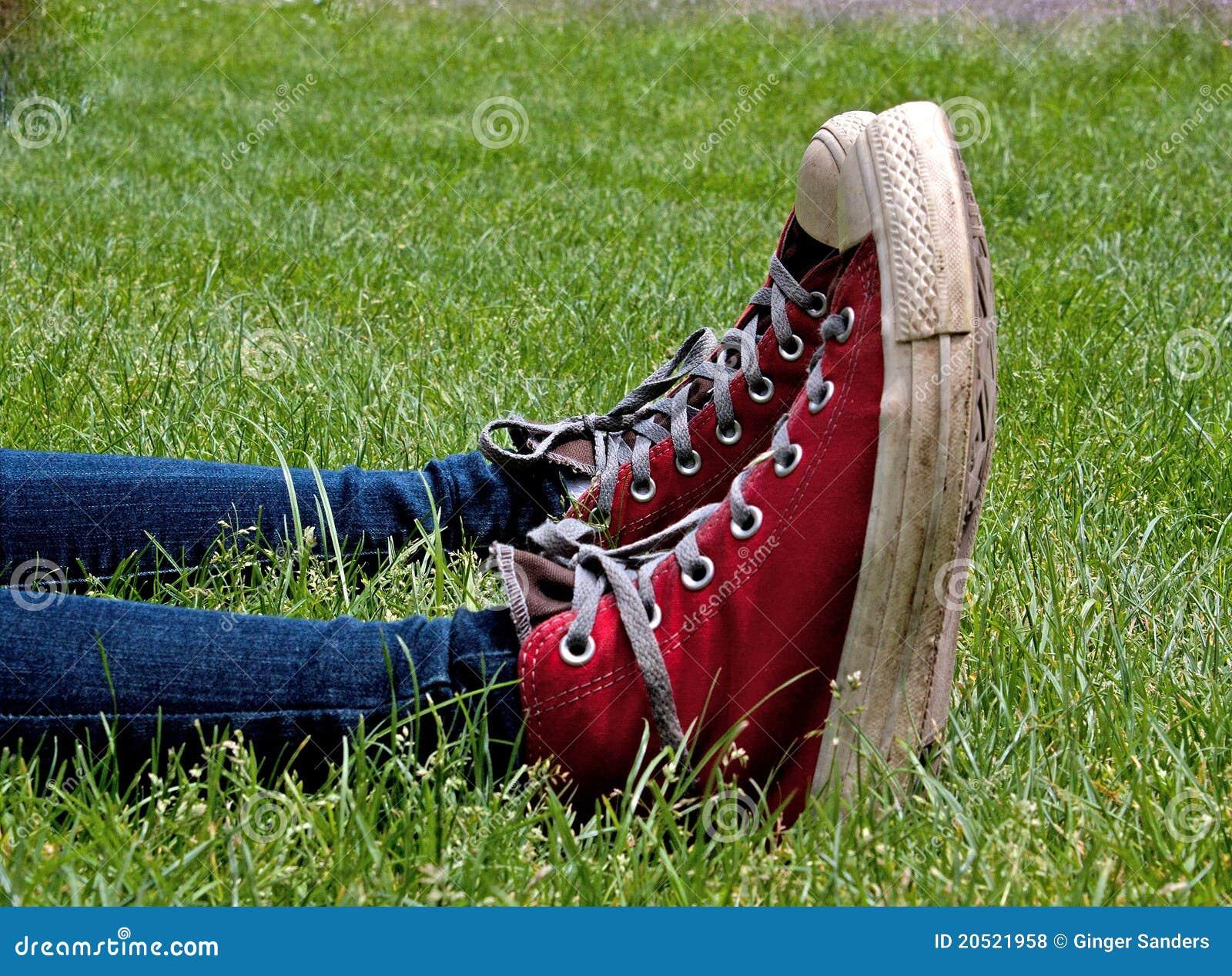 Sapatas de tênis superiores elevadas vermelhas paralelas na grama verde
