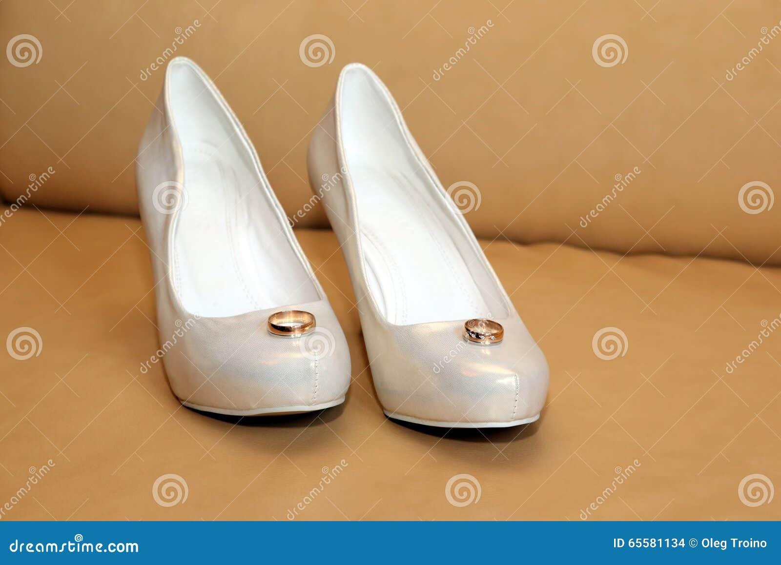 Sapatas do casamento da noiva com anéis