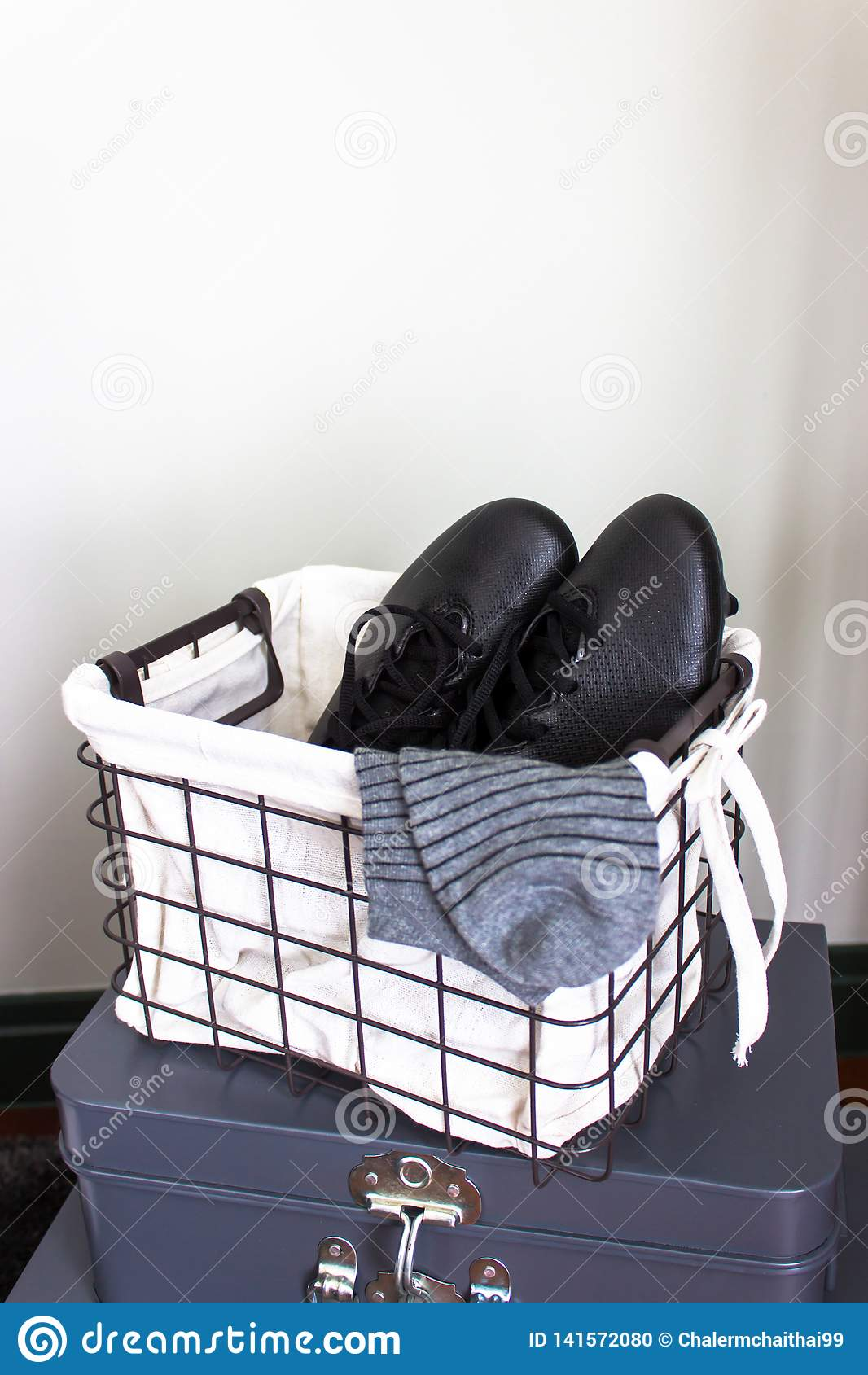 Sapatas do futebol na cesta com espaço da cópia