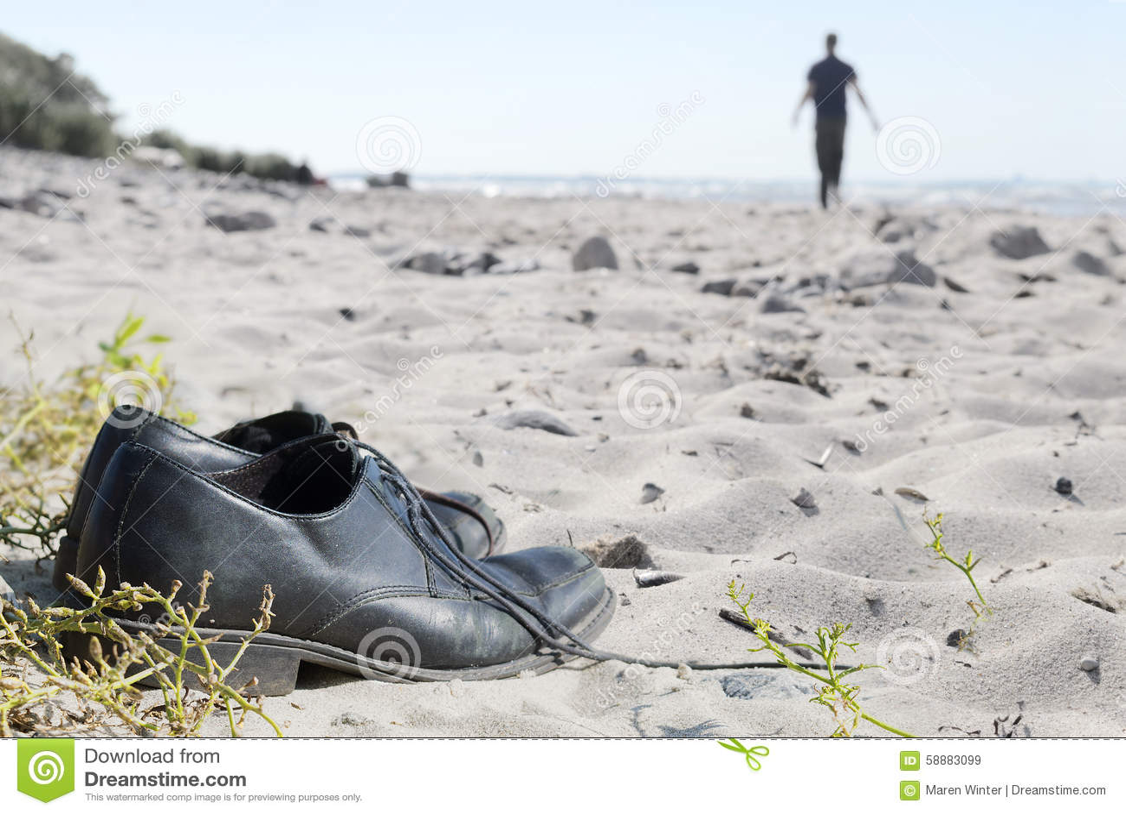 Sapatas do negócio na praia e um homem borrado que anda afastado ao th