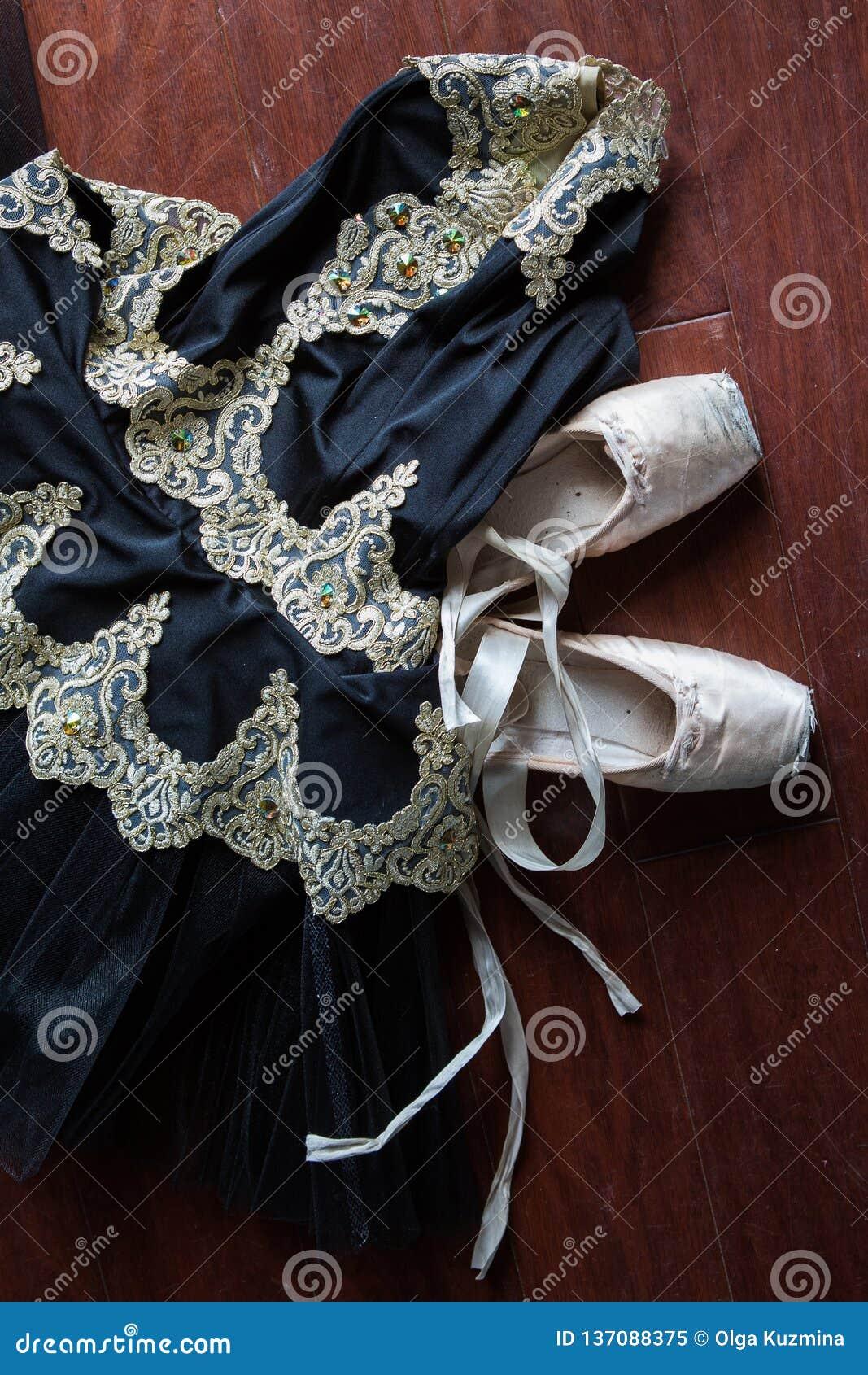 Sapatas do tutu e do pointe do bailado em um fundo do ensaio Sapatas velhas do pointe