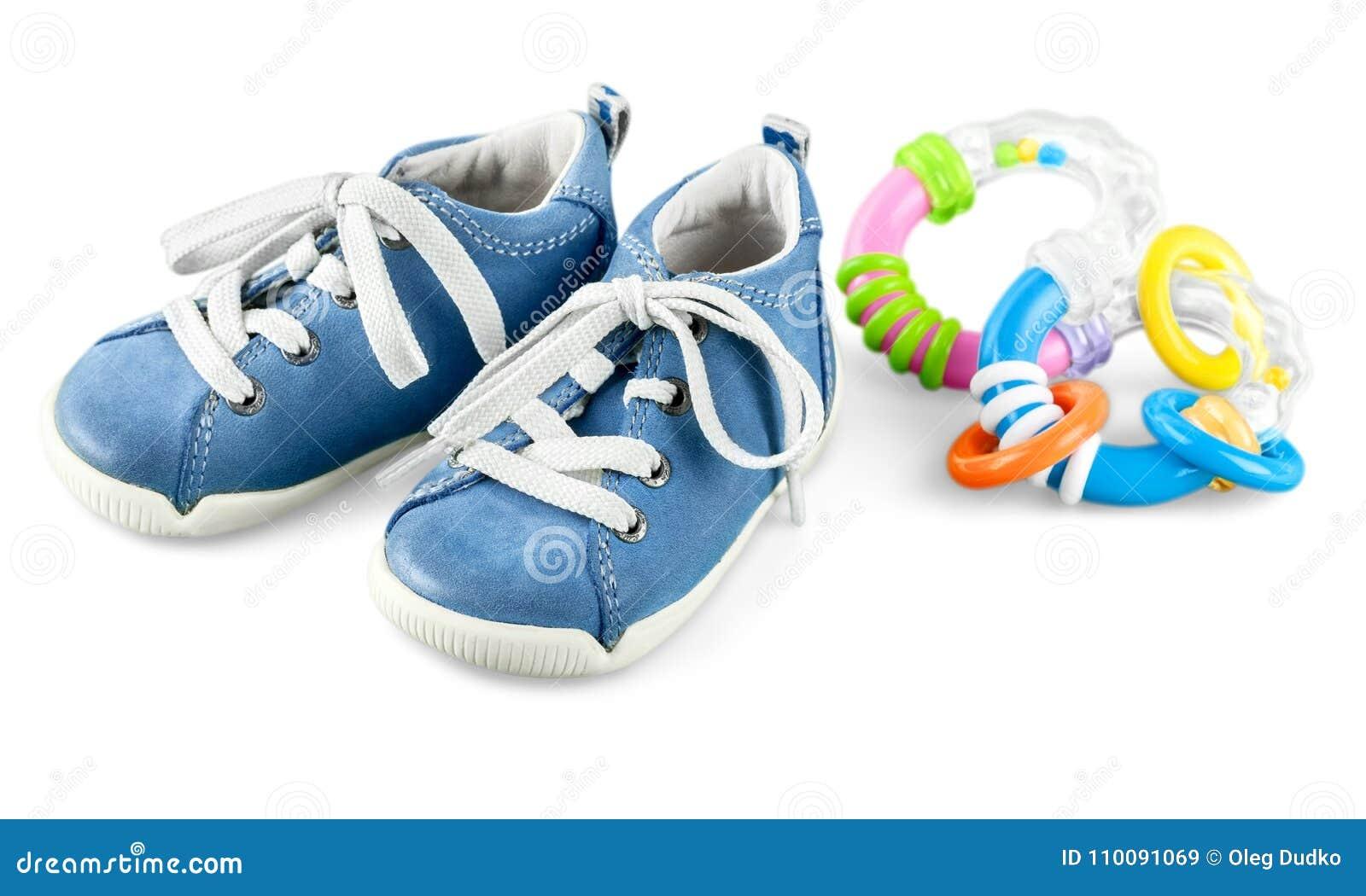 Sapatas e chocalho de bebê isolados no fundo branco