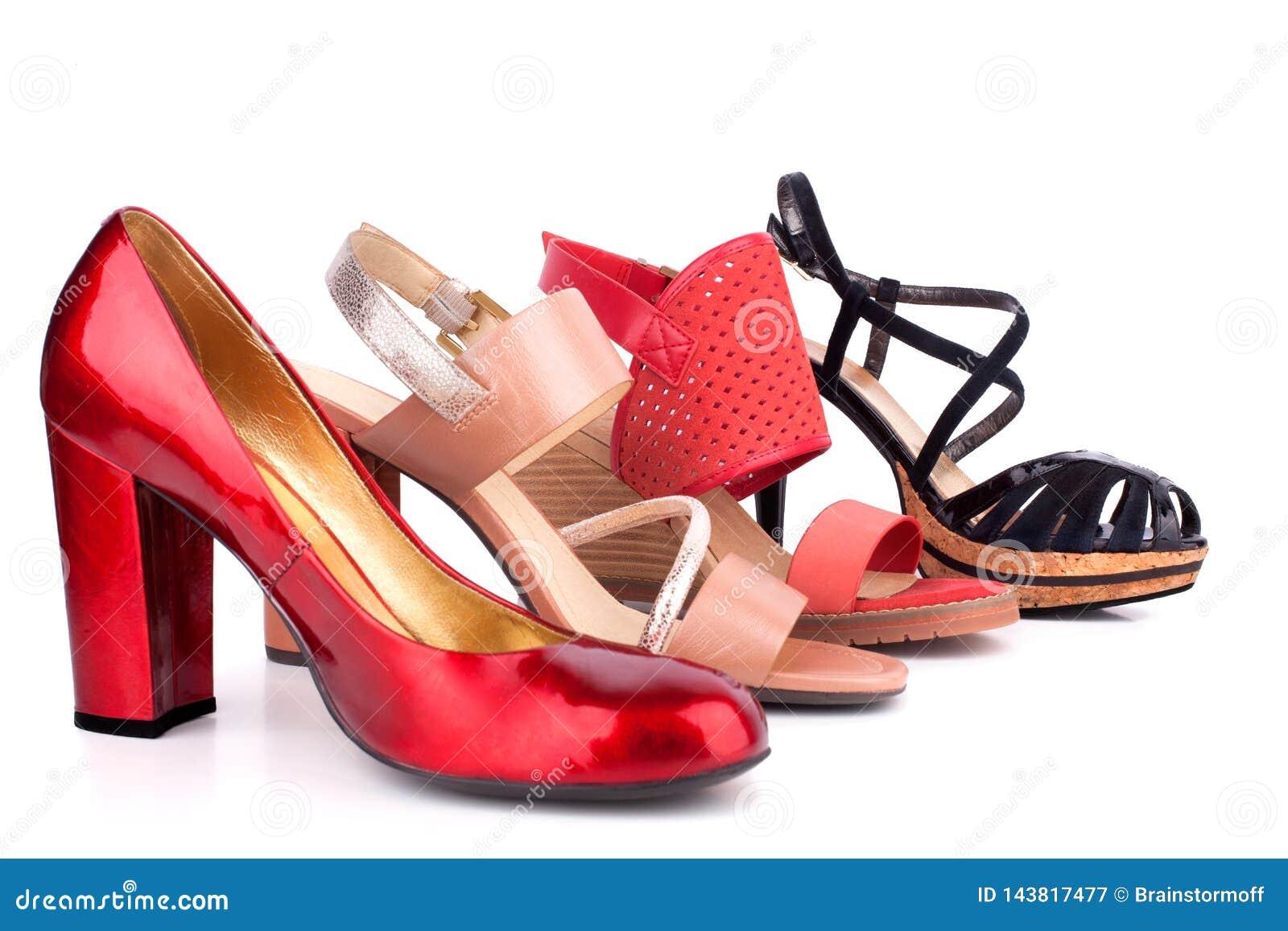 Sapatas e sandálias fêmeas vermelhas, bege, alaranjadas e pretas com os saltos altos para a opinião lateral da venda no fim branc