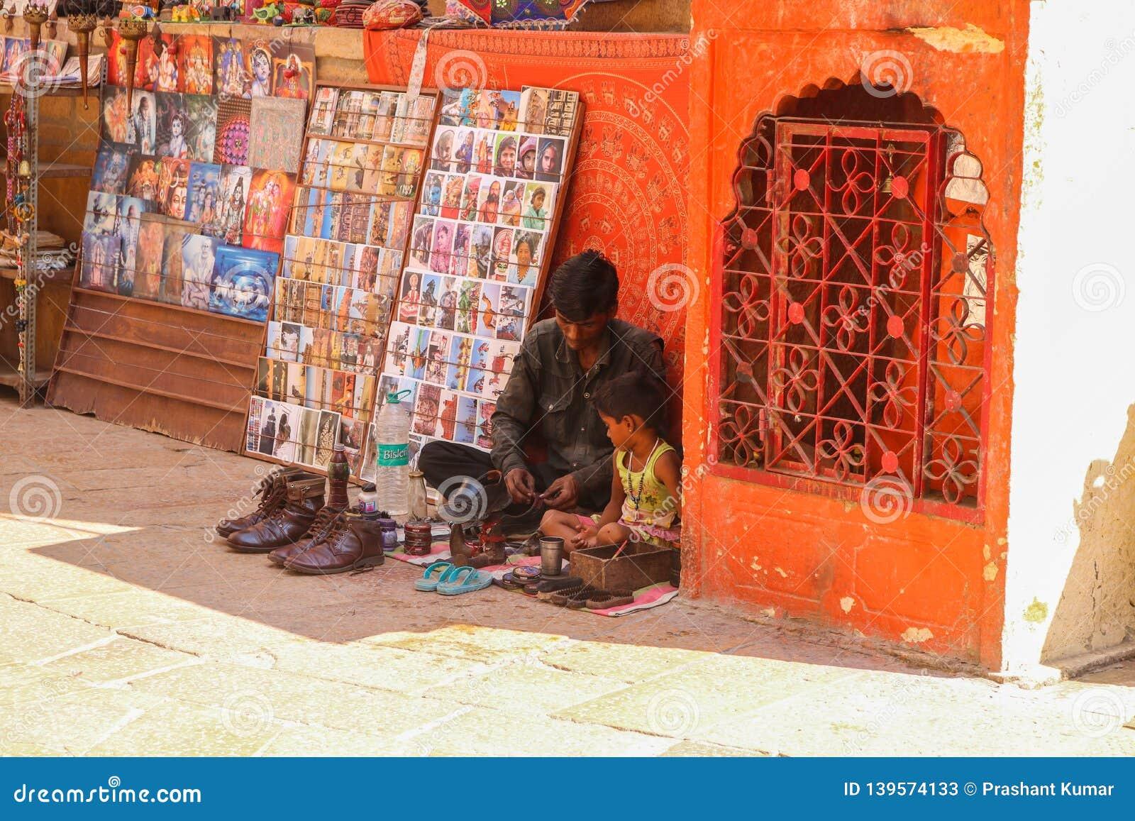 Sapateiro com seu ajuste da criança na rua de Jaisalmer