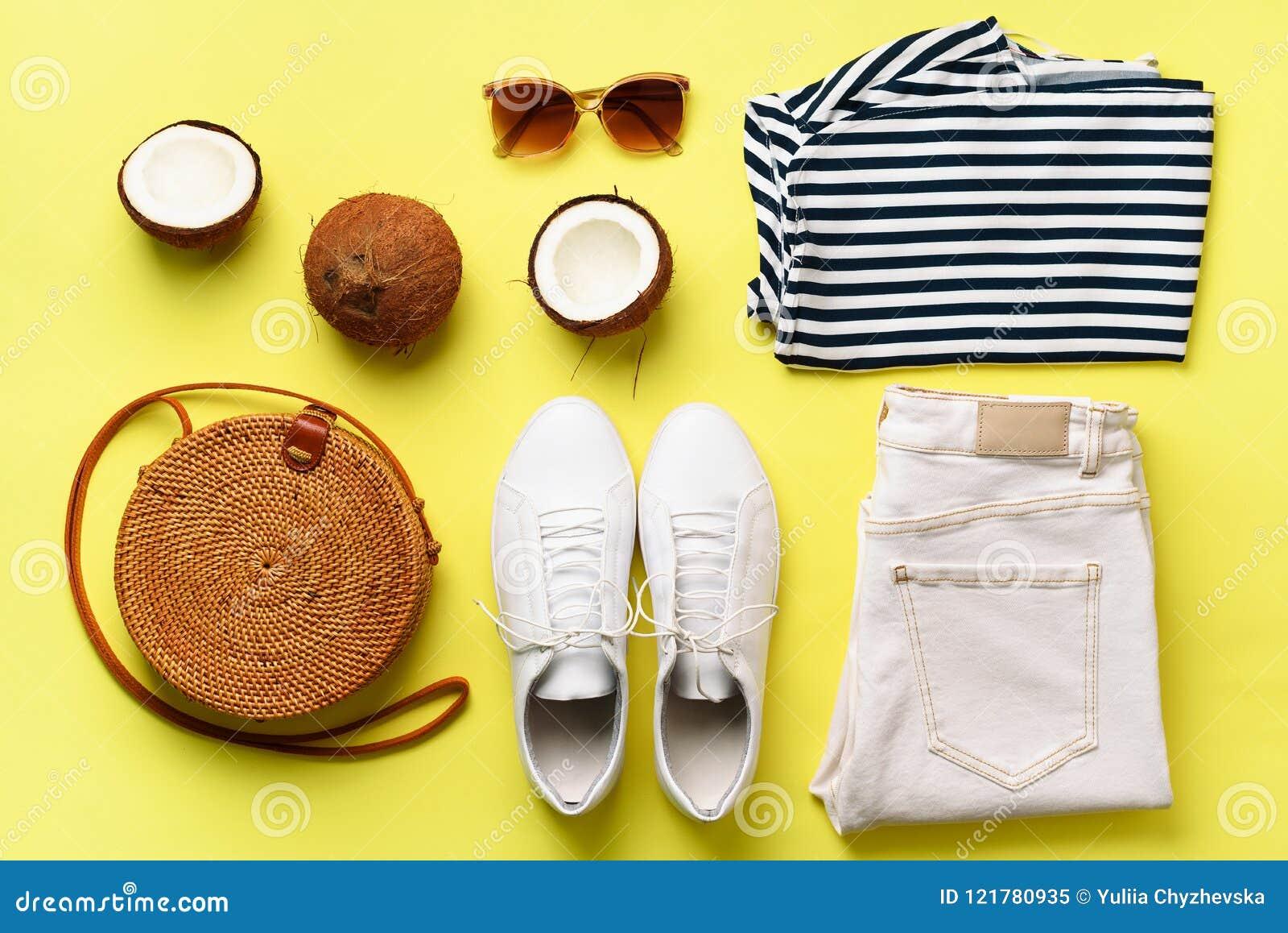 Sapatilhas brancas fêmeas, calças de brim, t-shirt listrado, saco do rattan, coco e óculos de sol no fundo amarelo com espaço da