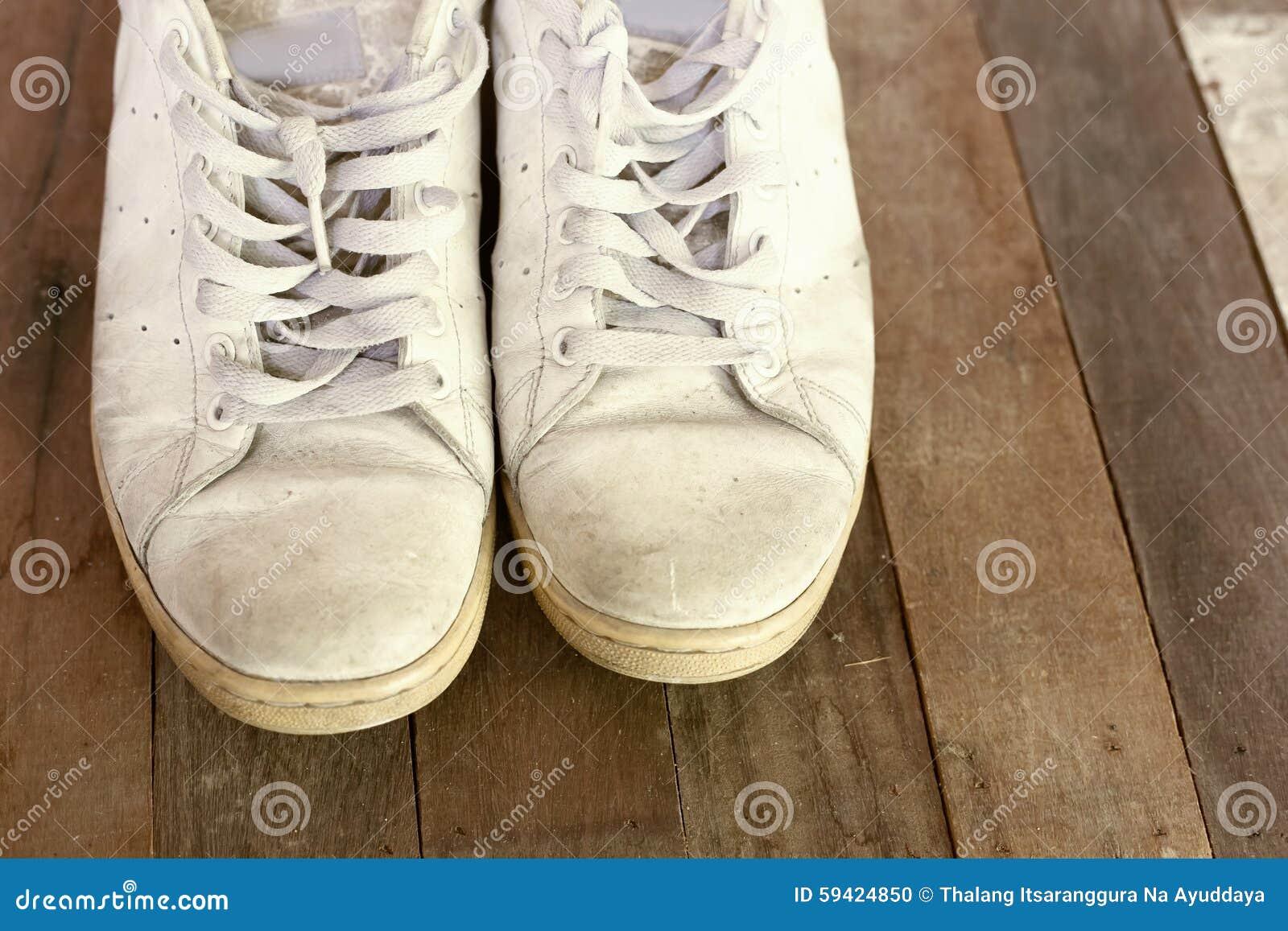 f91b1af728e Close up de um par de sapatilhas vistas de cima no assoalho de madeira