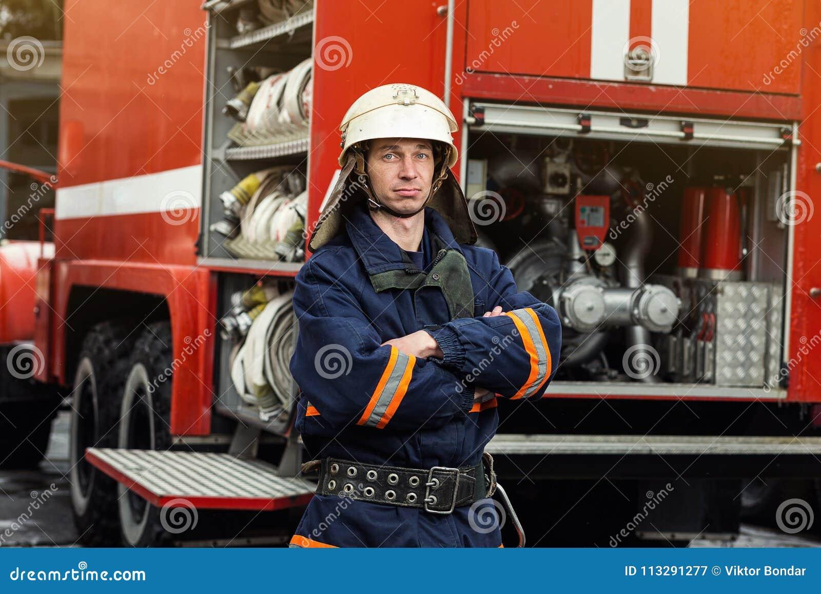 Sapeur-pompier de pompier dans l action se tenant près d un firetruck EMER