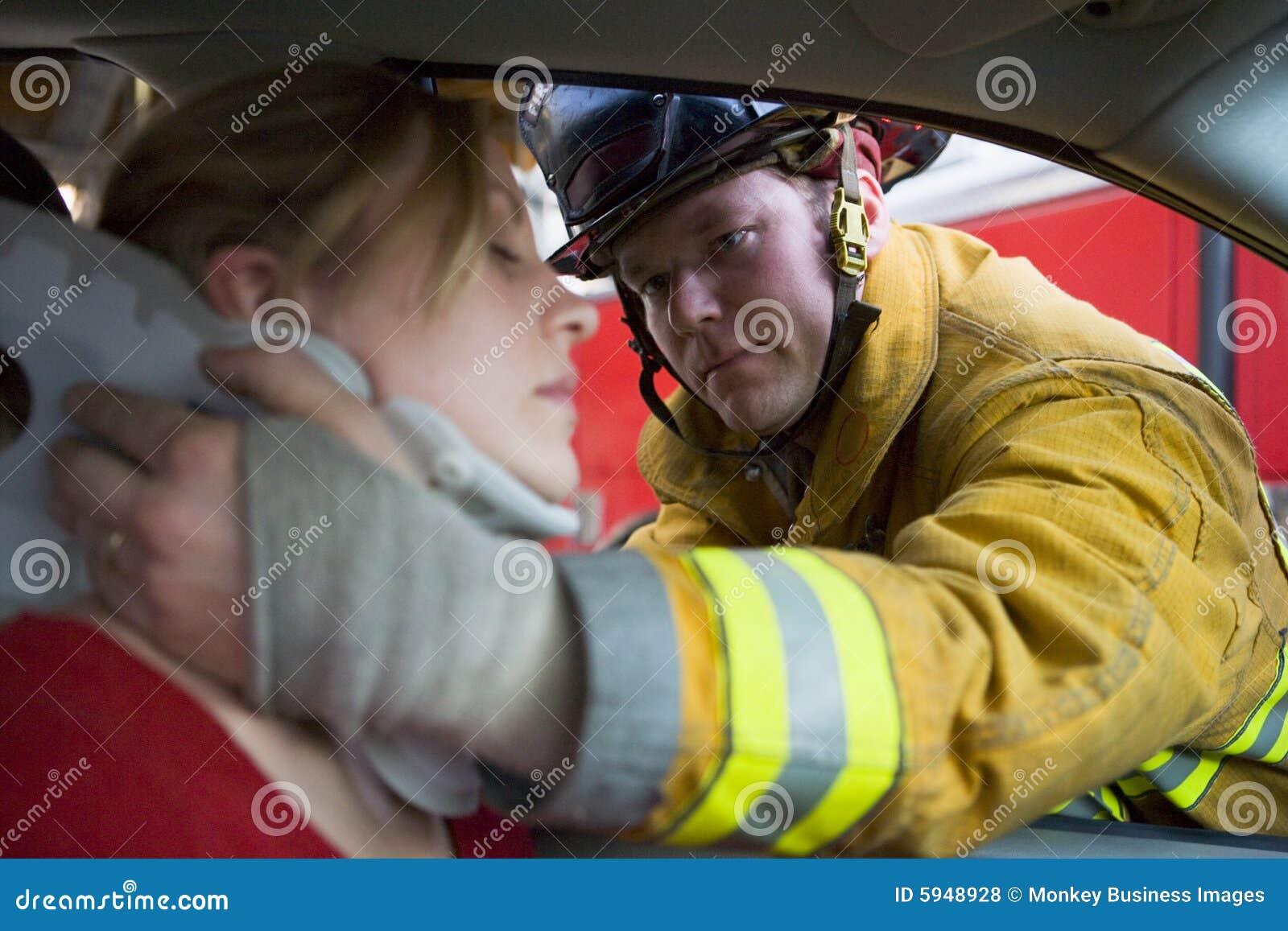 Sapeurs-pompiers de véhicule aidant le femme blessé