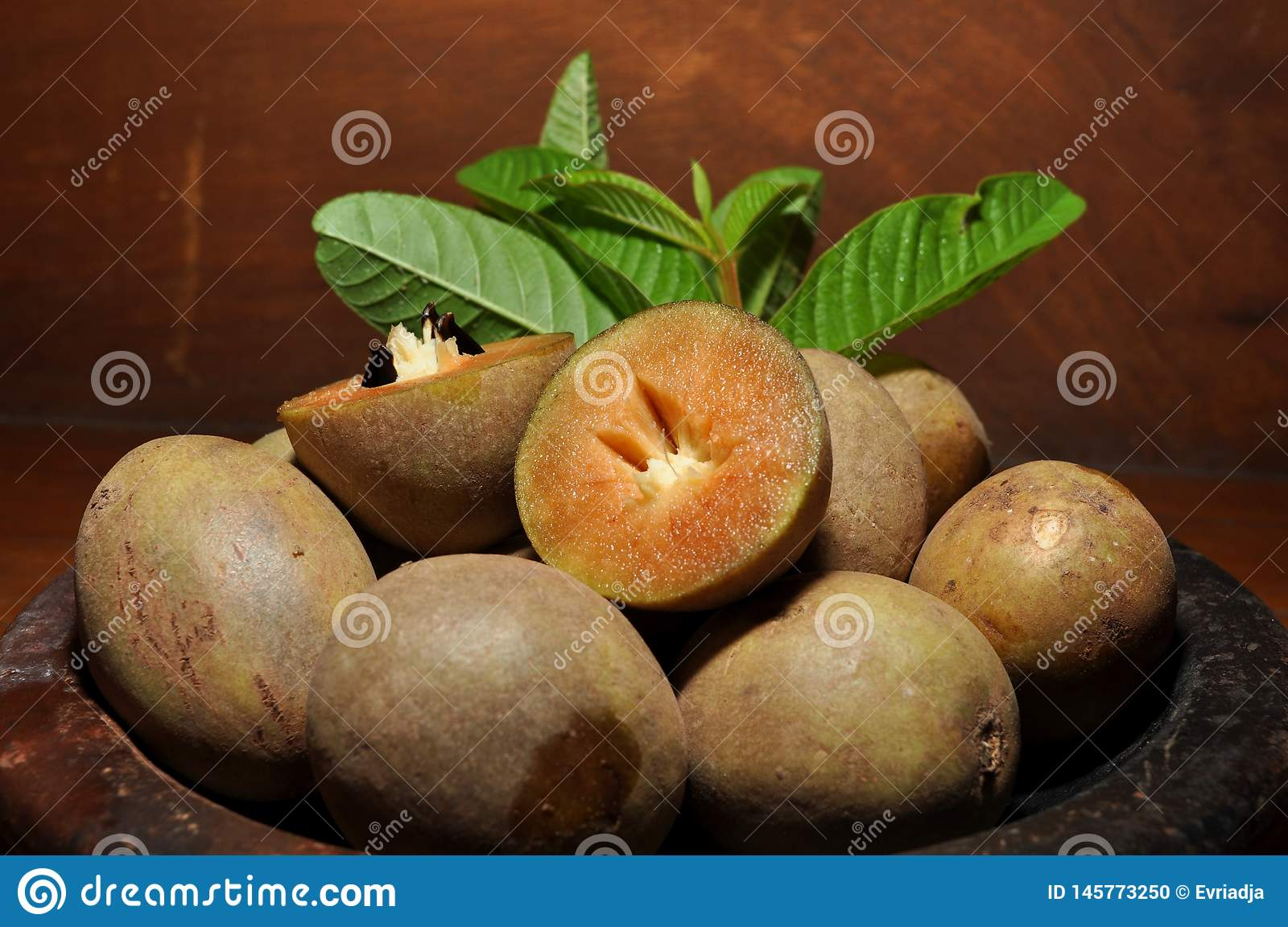 Sapodilla fruit with green leaves isolated on wooden background