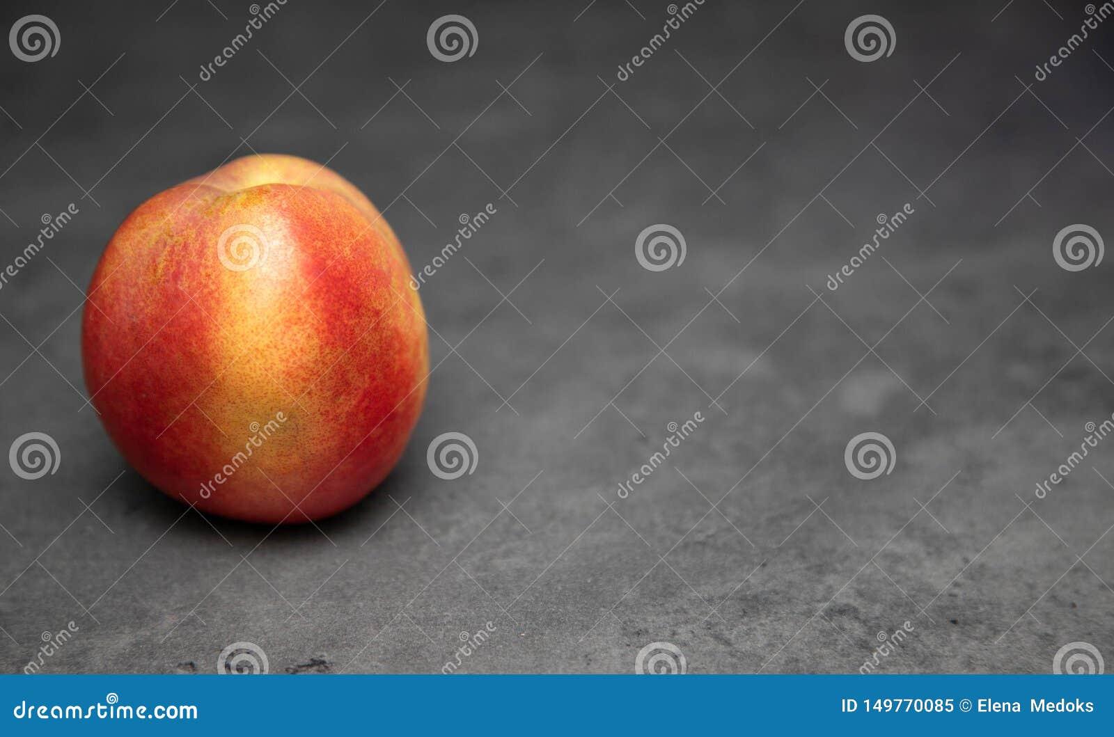 Sappige één, rijp, nectarine op een grijze achtergrond Nectarine op de lijst Plaats voor tekst