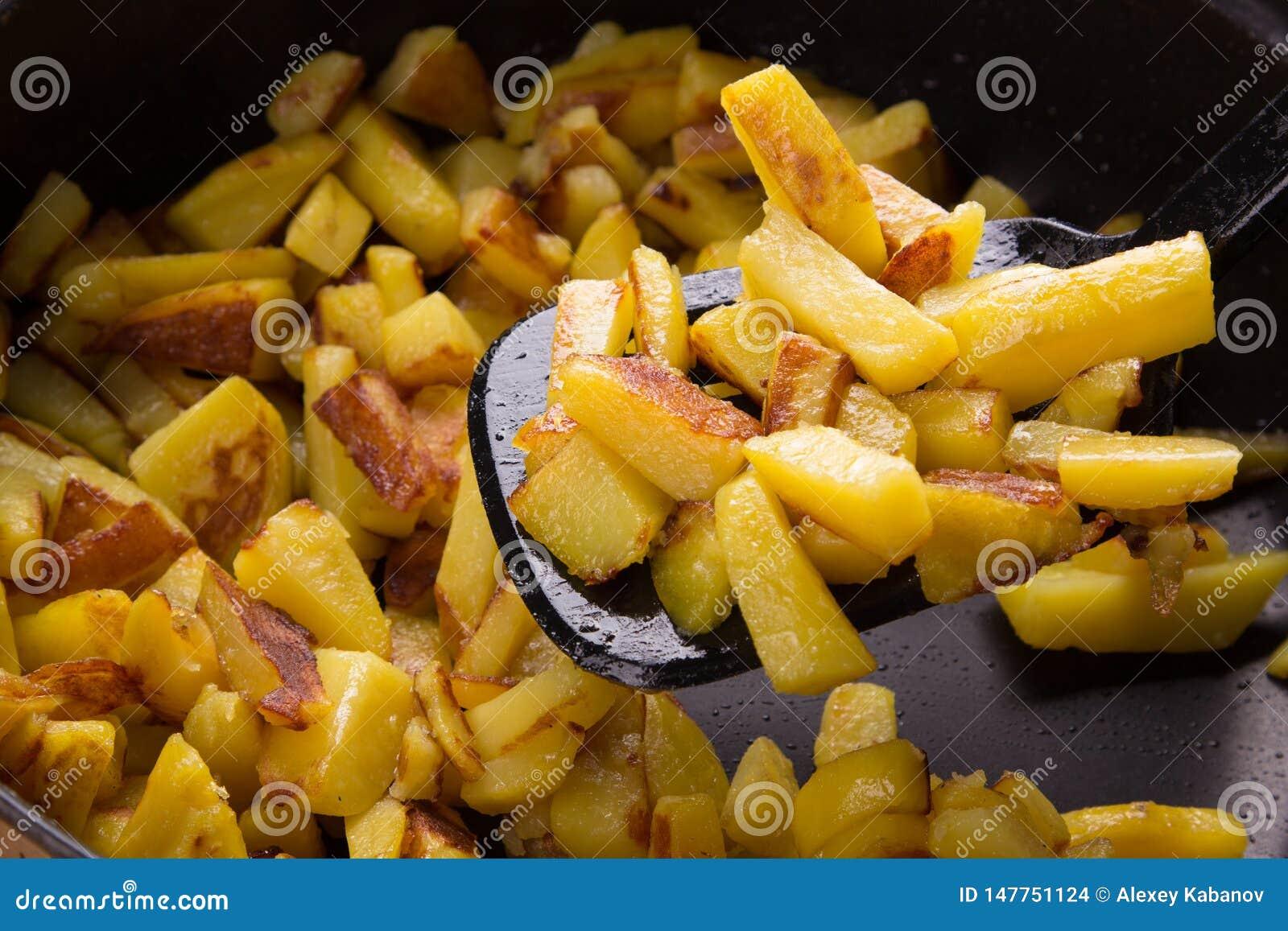 Sappige gebraden aardappels in een pan, eigengemaakte geroosterde aardappels met een knapperige dicht omhoog korst