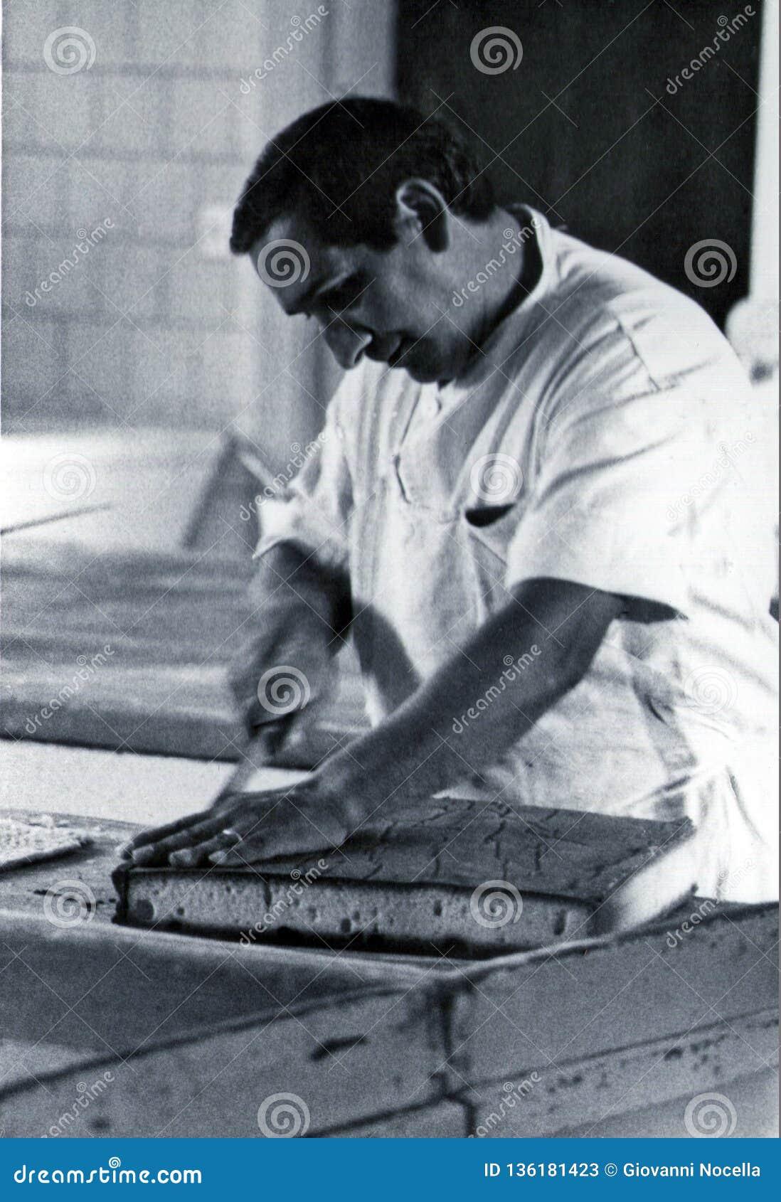 SARDEGNA, ИТАЛИЯ, 1970 - кондитер осторожно режет торт губки подготовленный в его мастерской
