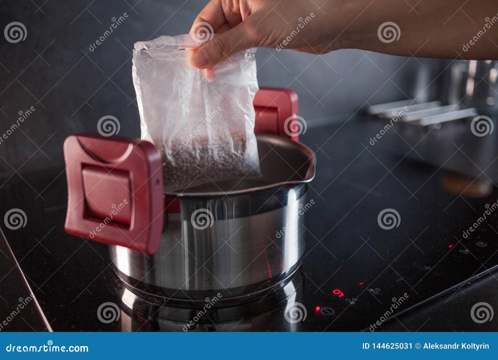 Sarrasin dans des sacs de partie pour la cuisson Faisant cuire le gruau de sarrasin, une femme met un sac pour faire cuire dans u