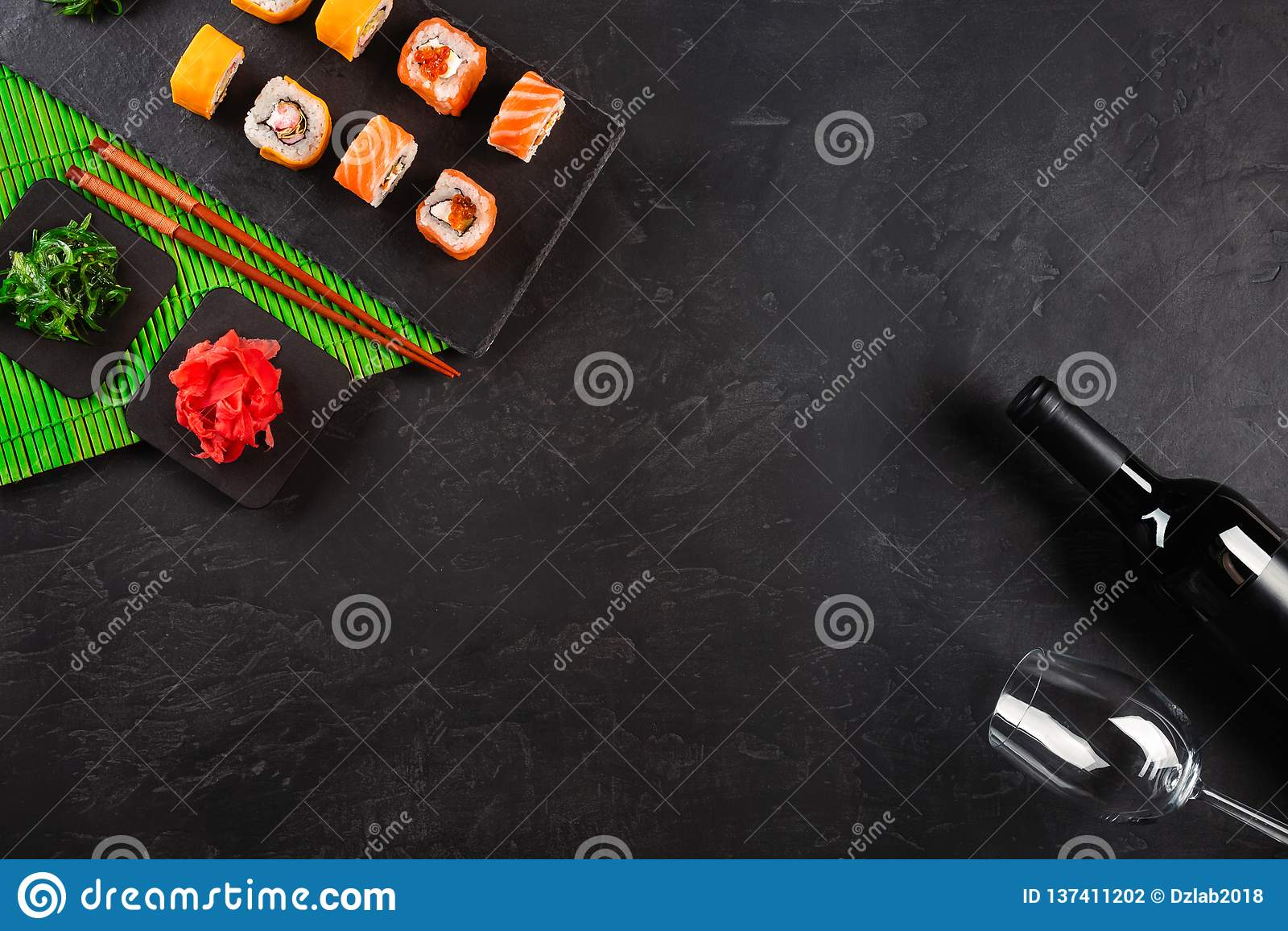 Sashimi dei sushi e rotoli di sushi stabiliti, bottiglia di vino e un vetro servito sull ardesia di pietra