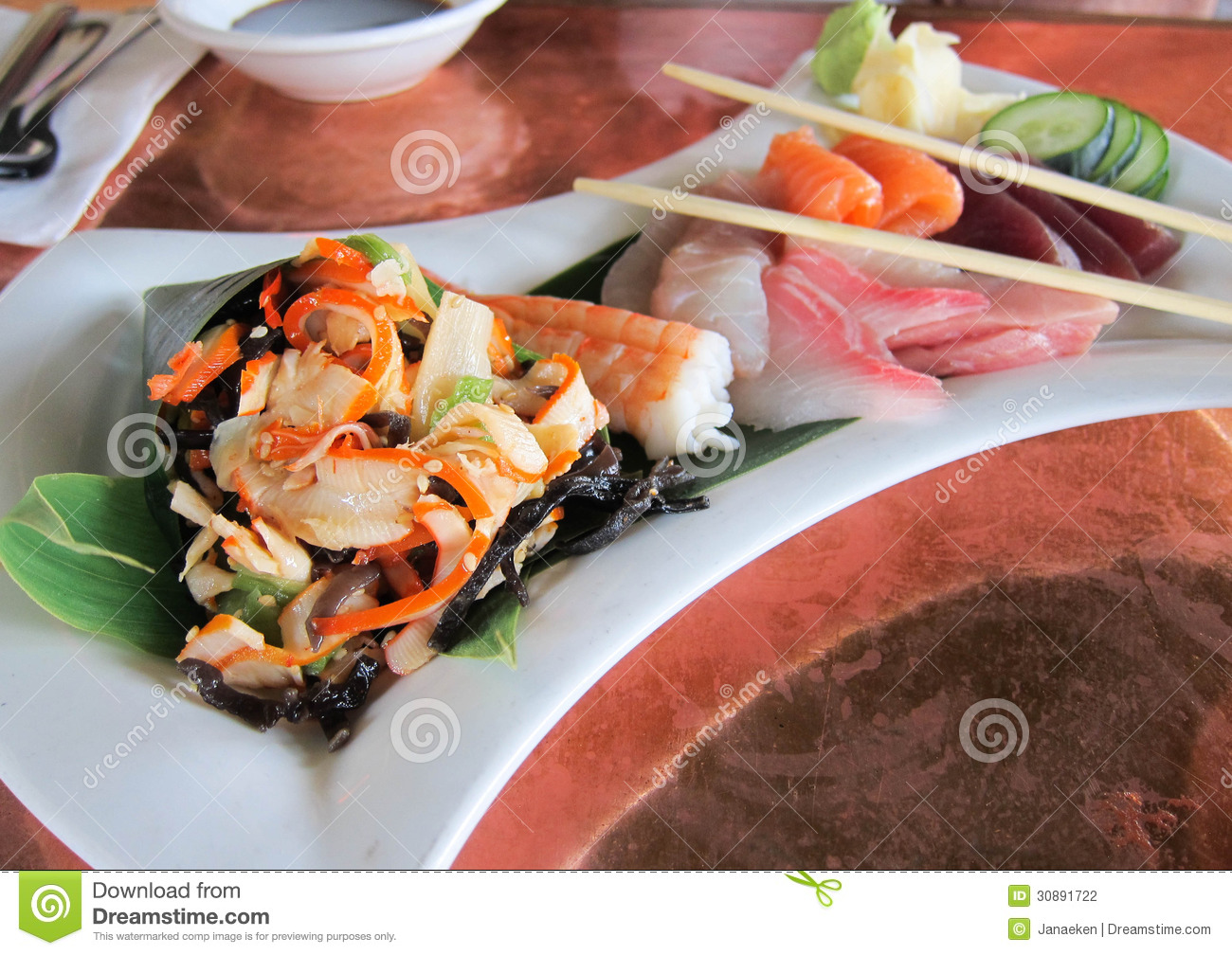 Sashimi, squid salad end vegetables served on a white plate. By ...
