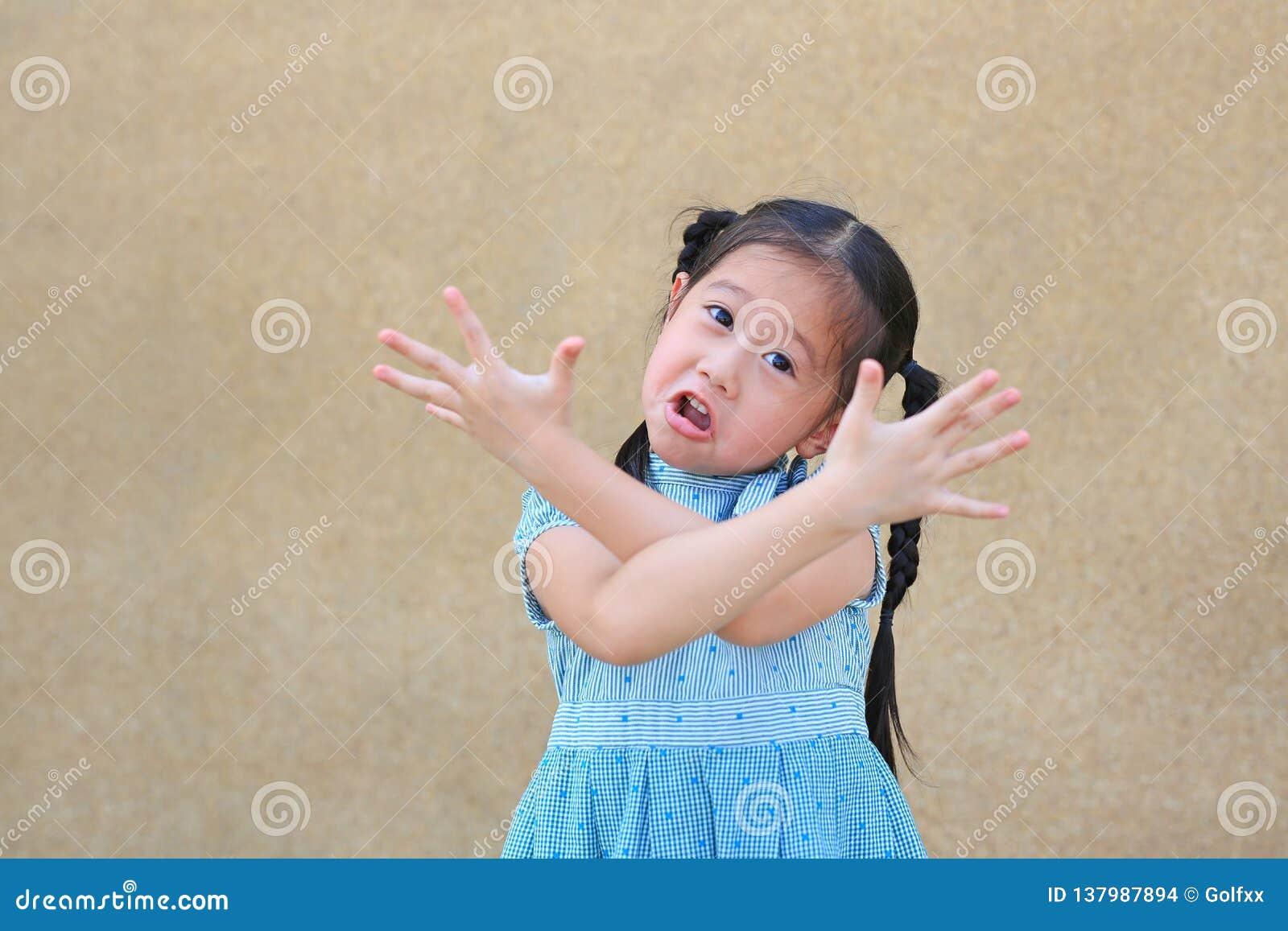 Sassy mała Azjatycka dzieciak dziewczyna z śmieszną twarzą i wyrażenie krzyżujemy one rękę