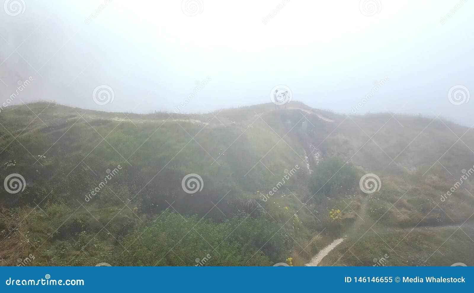 Satellietbeeld van mooi jong paar in witte kleren die zich op de bovenkant van klip dichtbij de afgrond in een zware mist bevinde