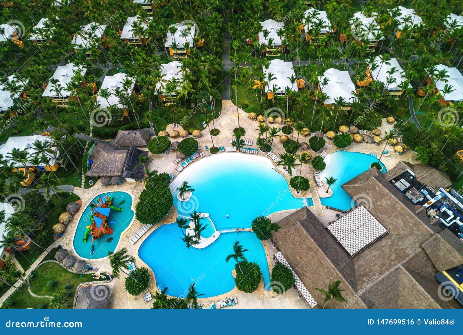 Satellietbeeld van tropische zwembad en palmen in luxetoevlucht