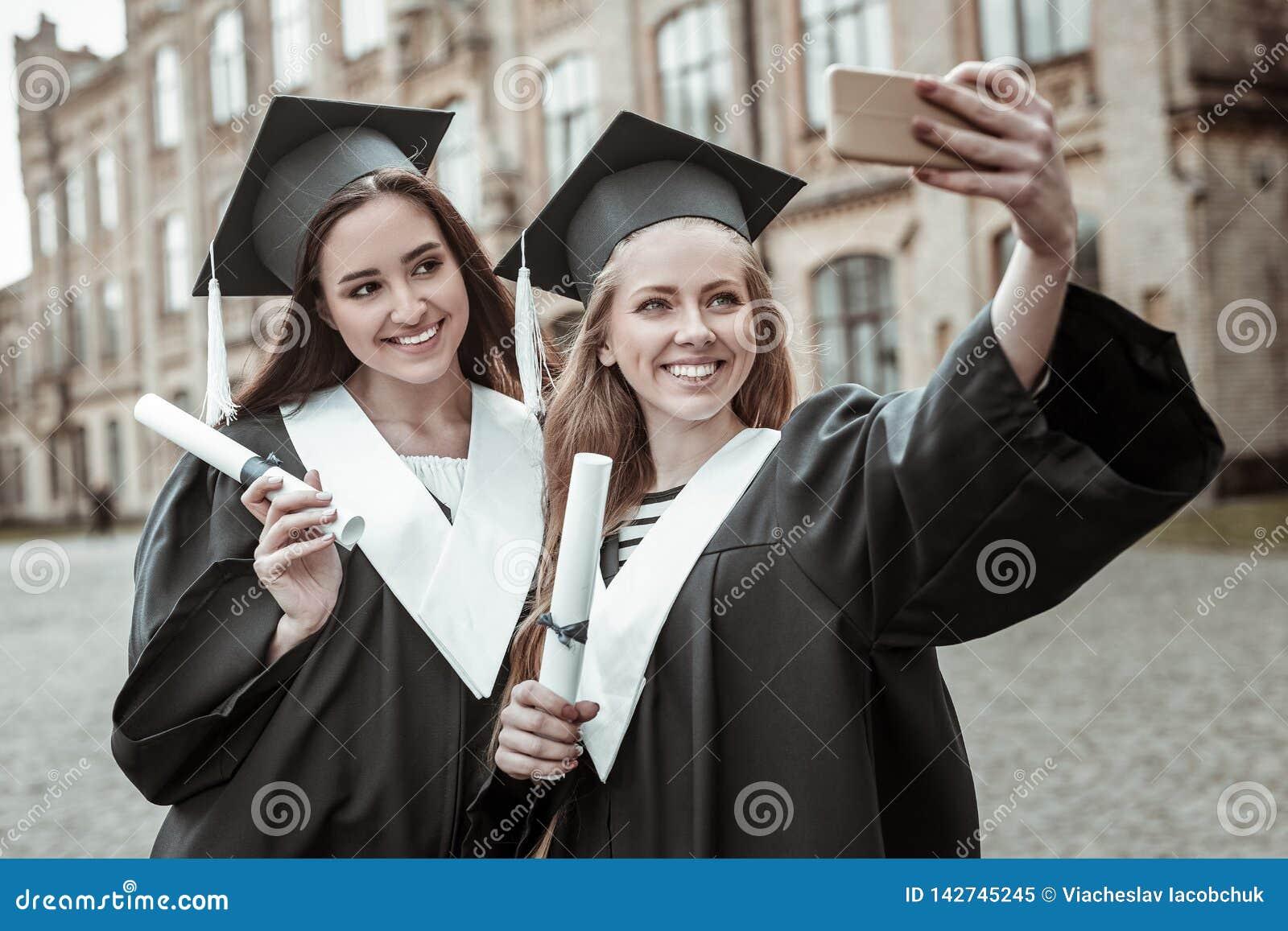 Satisfecho dos hembras que hacen la foto del selfie junto