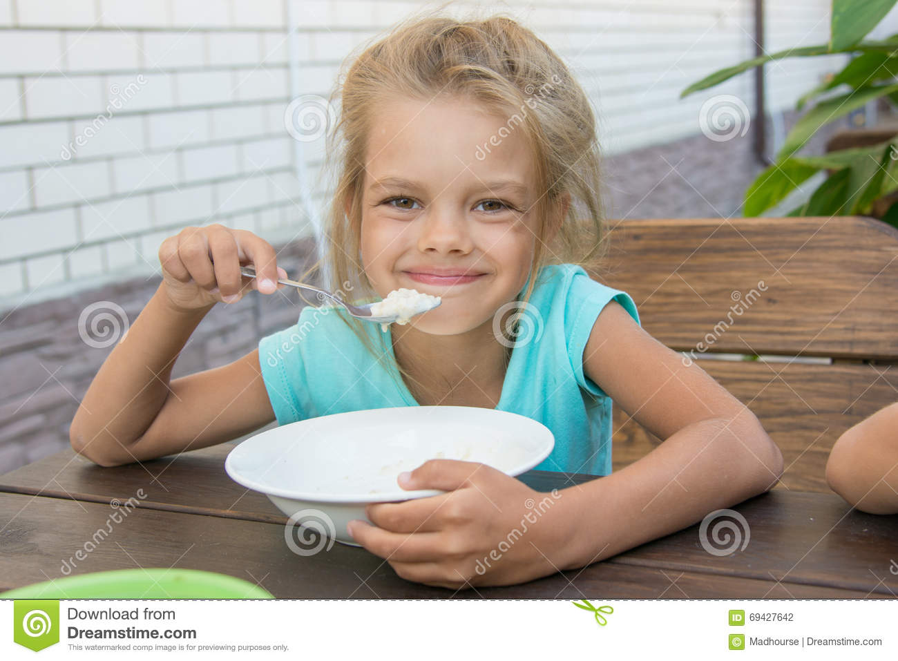 Satisfied Six Year Old Girl At Table In The Courtyard