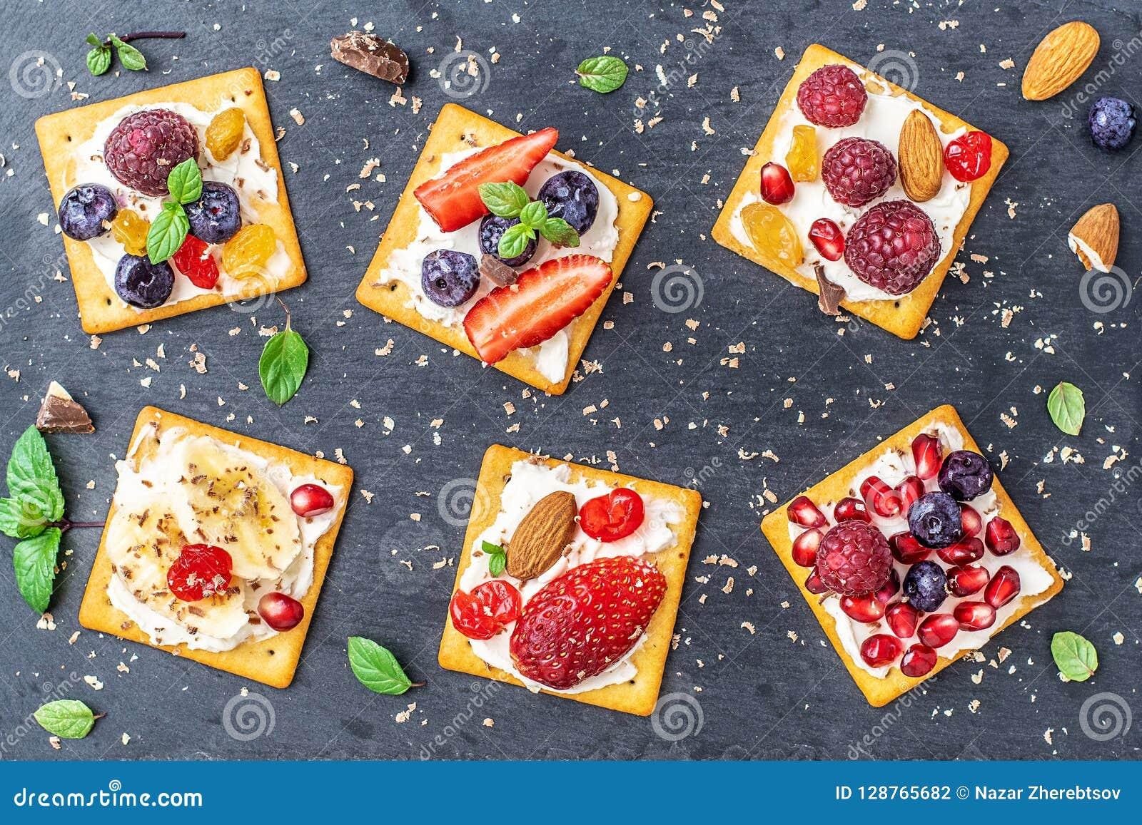 Satz Cracker mit verschiedener Fruchtnahaufnahme auf schwarzer Steinplatte