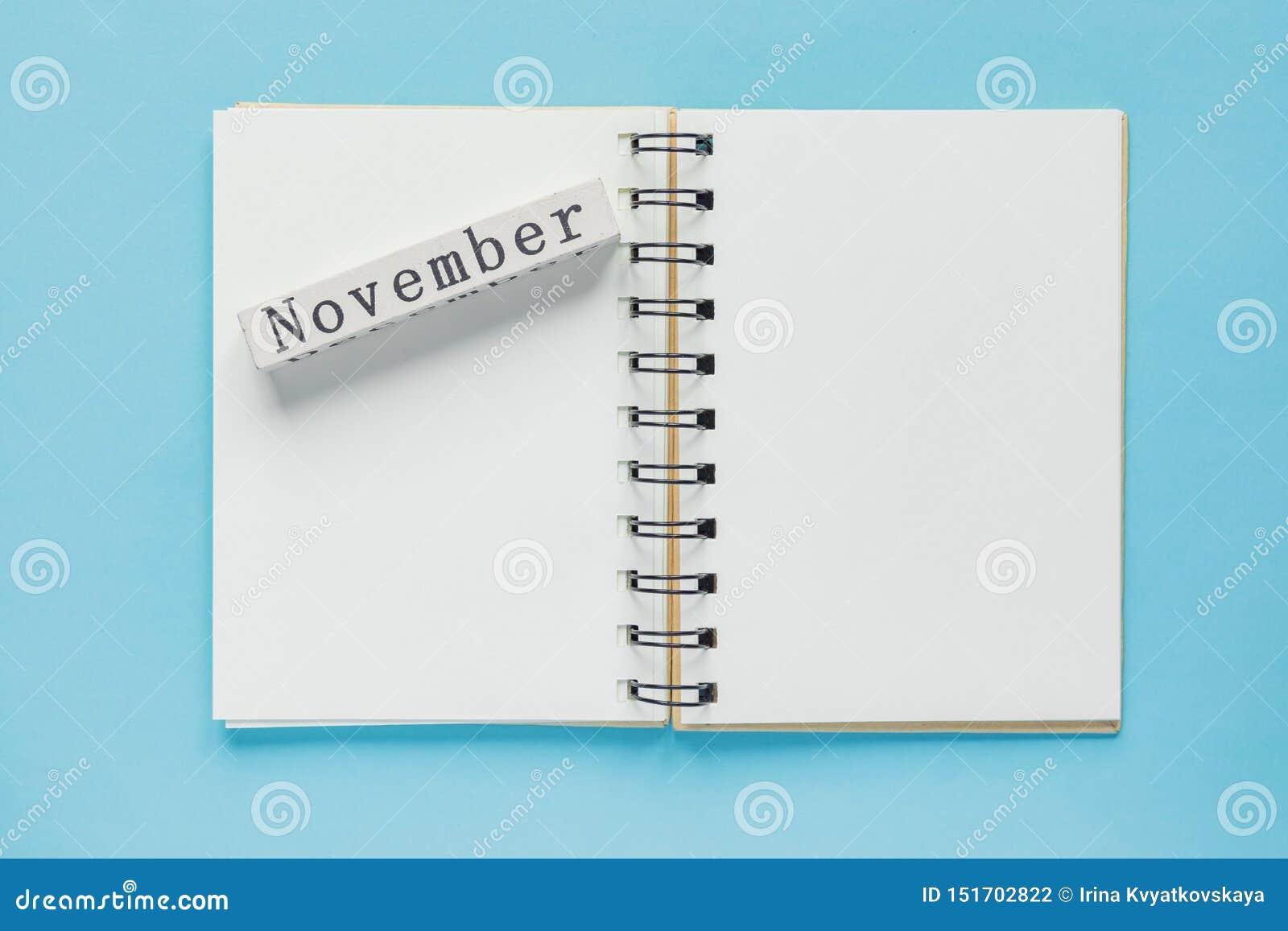 Sauberes gewundenes Anmerkungsbuch für Anmerkungen und Mitteilungen und hölzerne Kalenderstange Novembers auf blauem Hintergrund